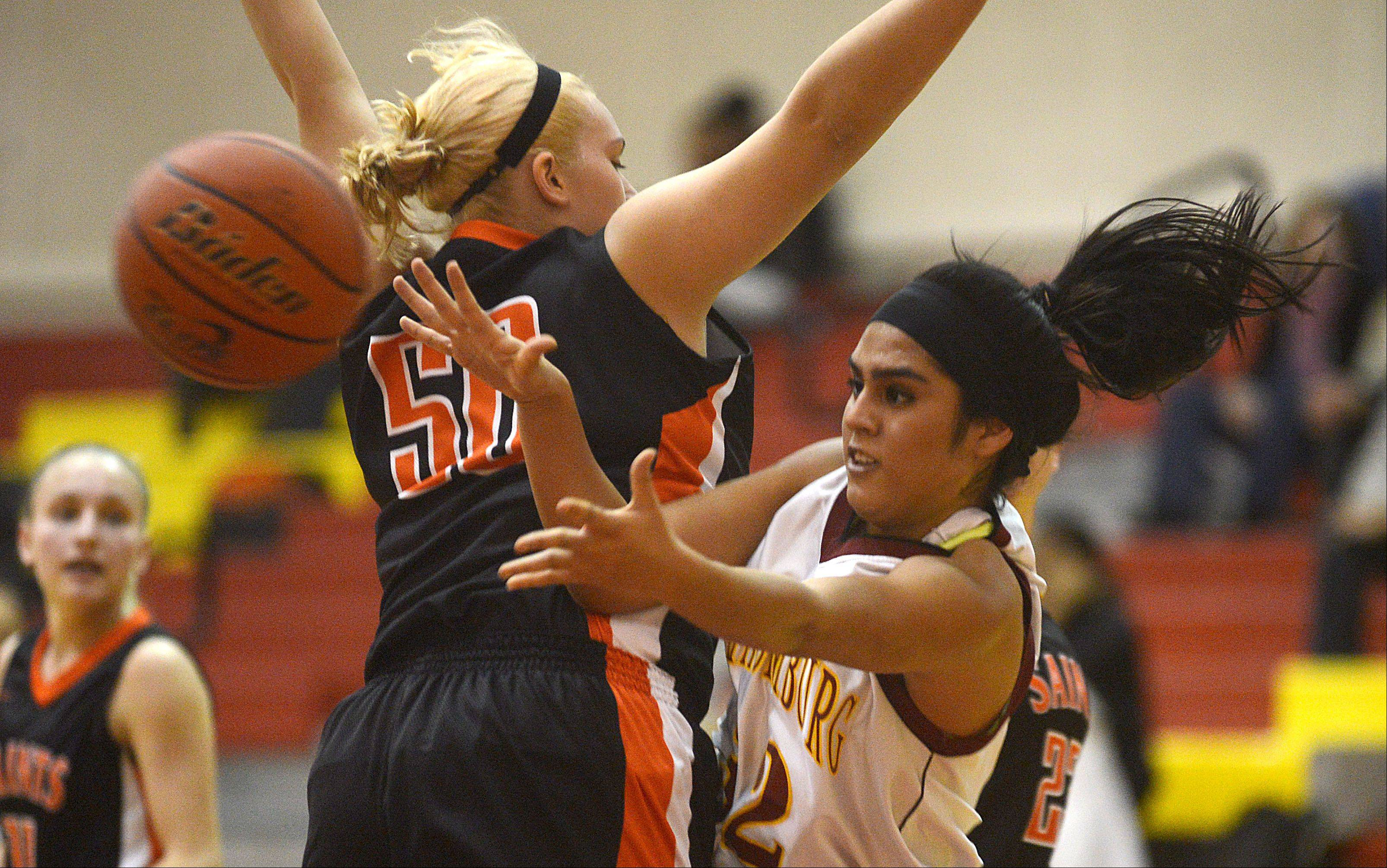 St. Charles East's Chloe John plays defense as Schaumburg's Lillian Chavarria, right, dishes the ball past during a varsity girls basketball game at Schaumburg High School on Monday evening.