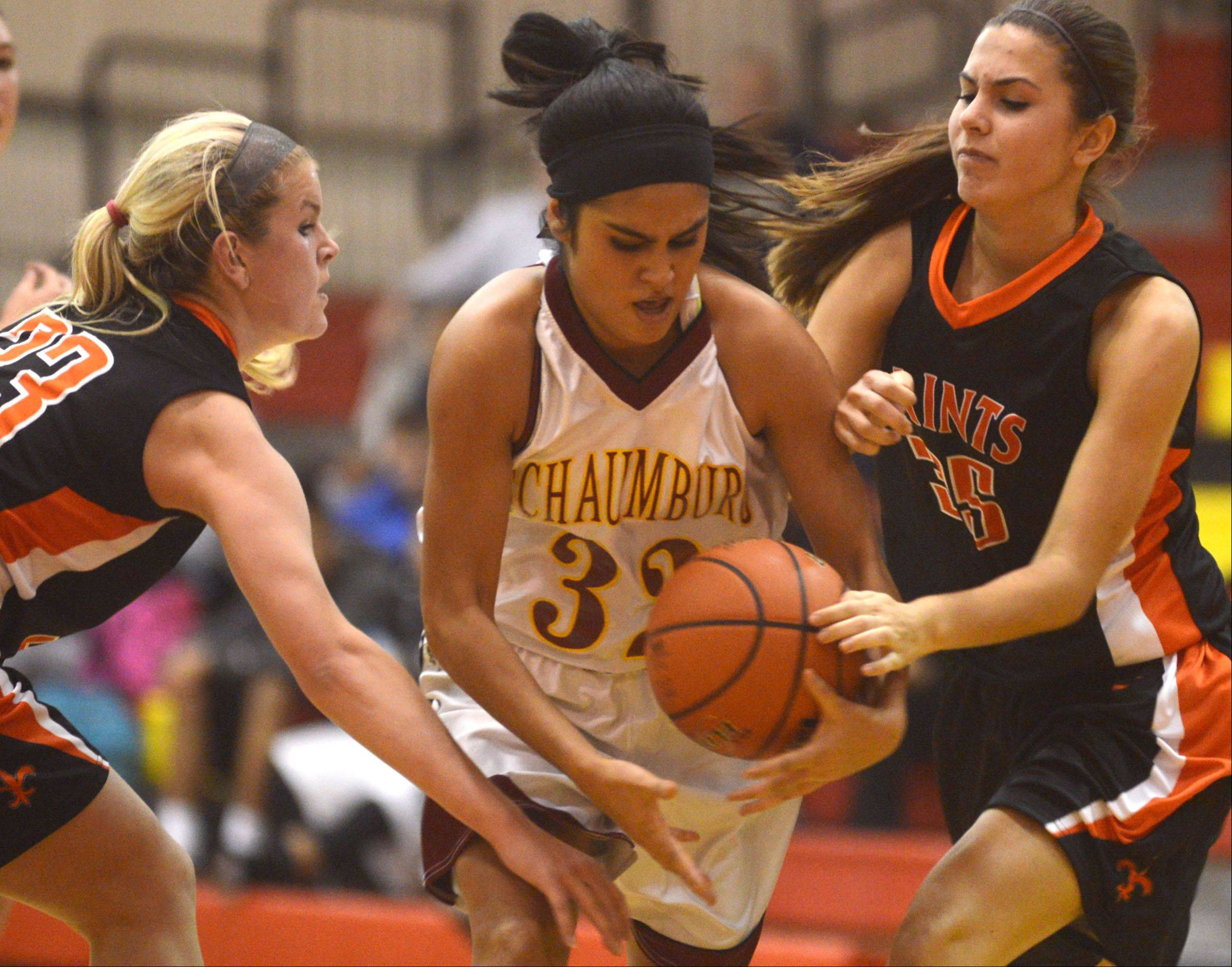St. Charles East's Hannah Nowling, left, and Hannah Vitkus, right, try to stop Schaumburg's Lillian Chavarria, center, during a varsity girls basketball game at Schaumburg High School on Monday evening.