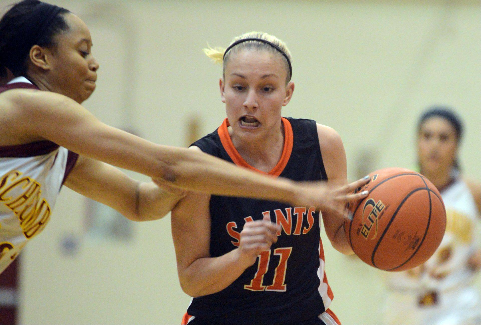 St. Charles East's Katelyn Claussner, right, tries to get past Schaumburg's Jada Blackwell, left, during a varsity girls basketball game at Schaumburg High School on Monday evening.