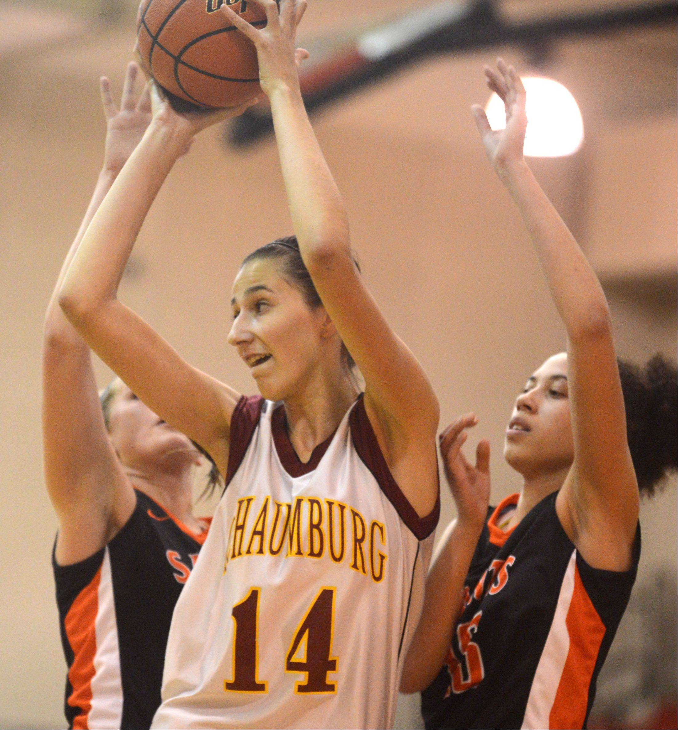 Schaumburg's Tatiana Doroskin, center, looks for a place to pass the ball against St. Charles East's Kyra Washington, right, during a varsity girls basketball game at Schaumburg High School on Monday evening.
