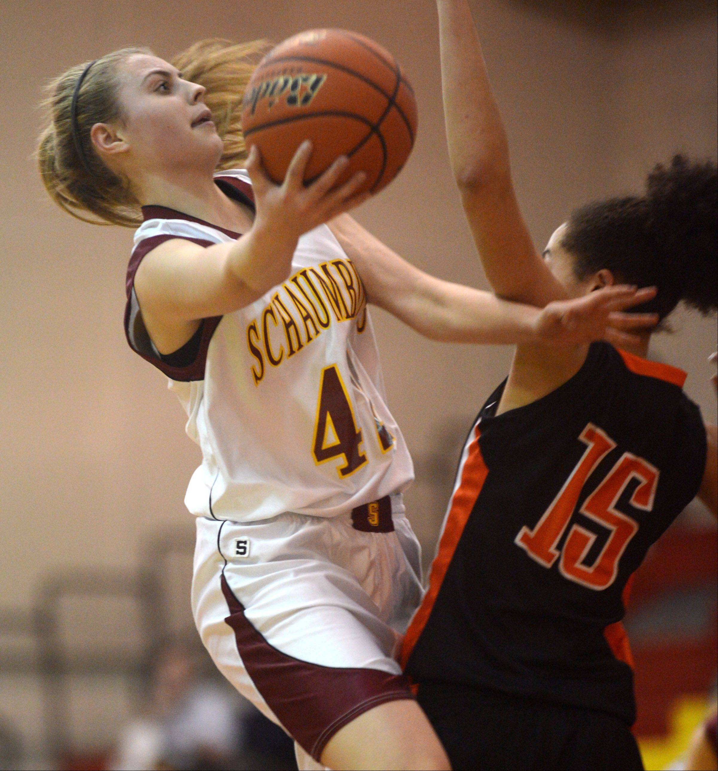 St. Charles East's Kyra Washington, right, tries to stop Schaumburg's Mallory Gerber, left from scooping the ball to the hoop during a varsity girls basketball game at Schaumburg High School on Monday evening.
