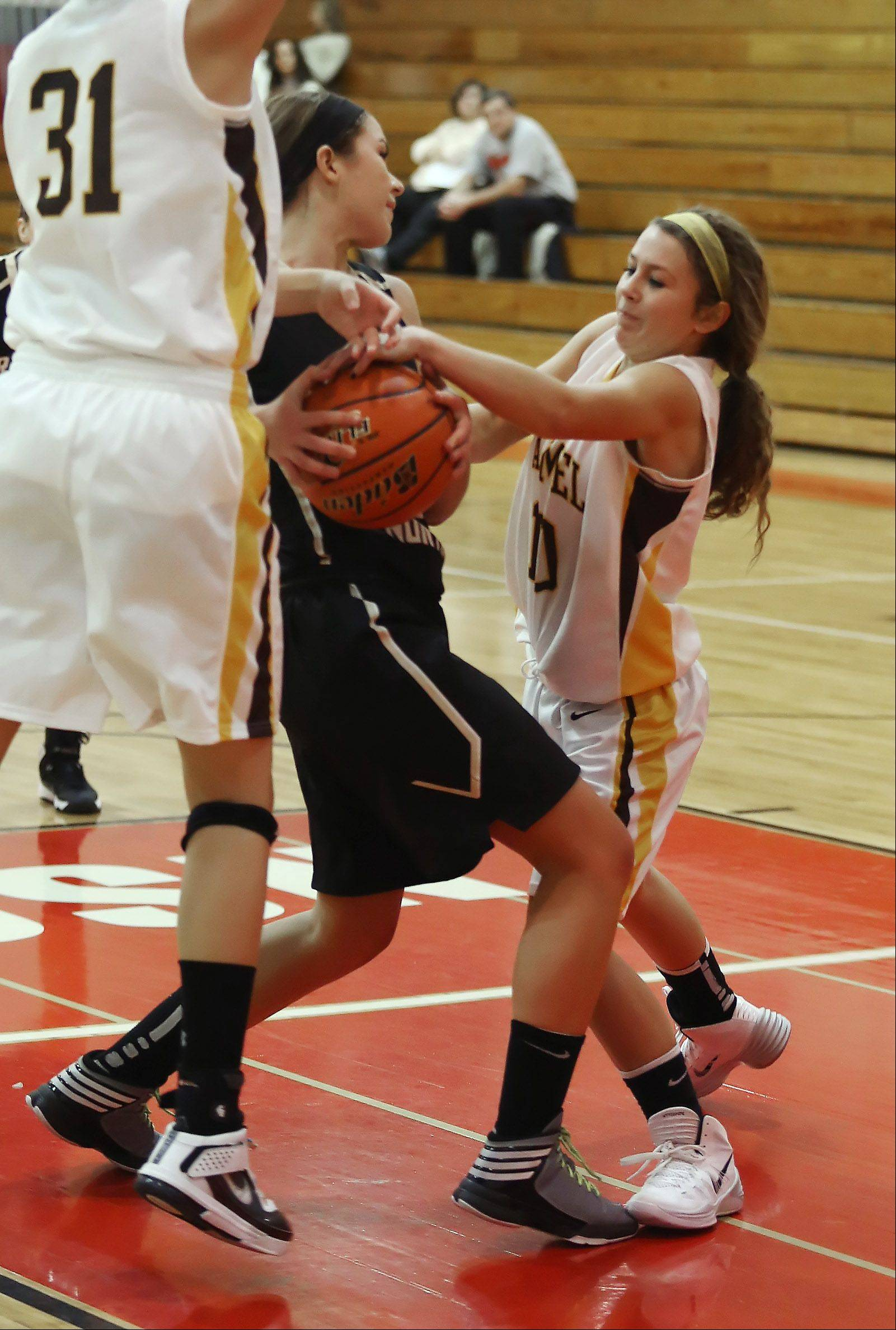 Carmel guard Sam Melillo tries to take the ball from Grayslake North forward Ella Swanson on Monday in the Mundelein tournament.