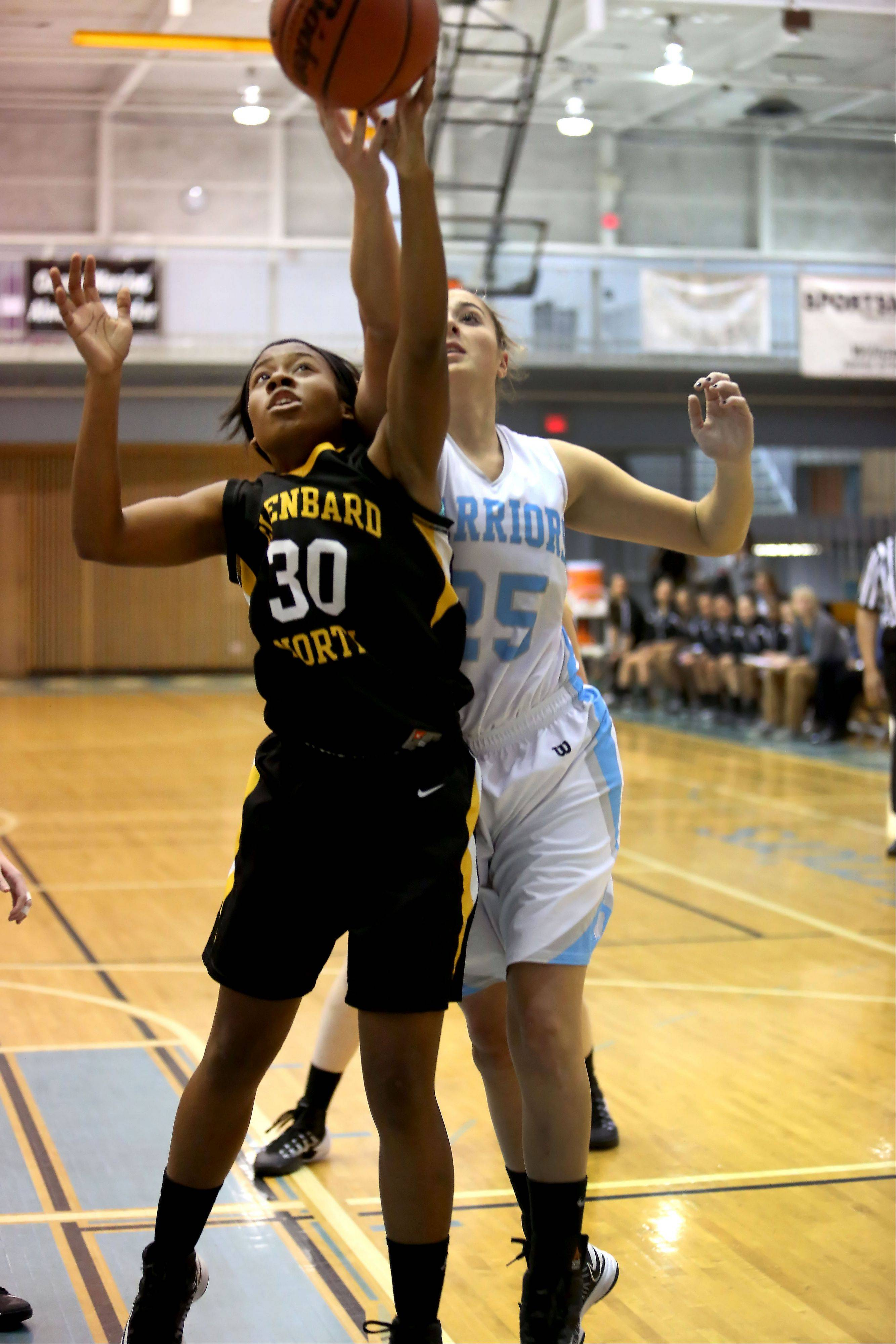 Liala Pickens, left, of Glenbard North and Samantha Schmidt, right, of Willowbrook go up for a rebound during girls basketball on Tuesday in Villa Park.