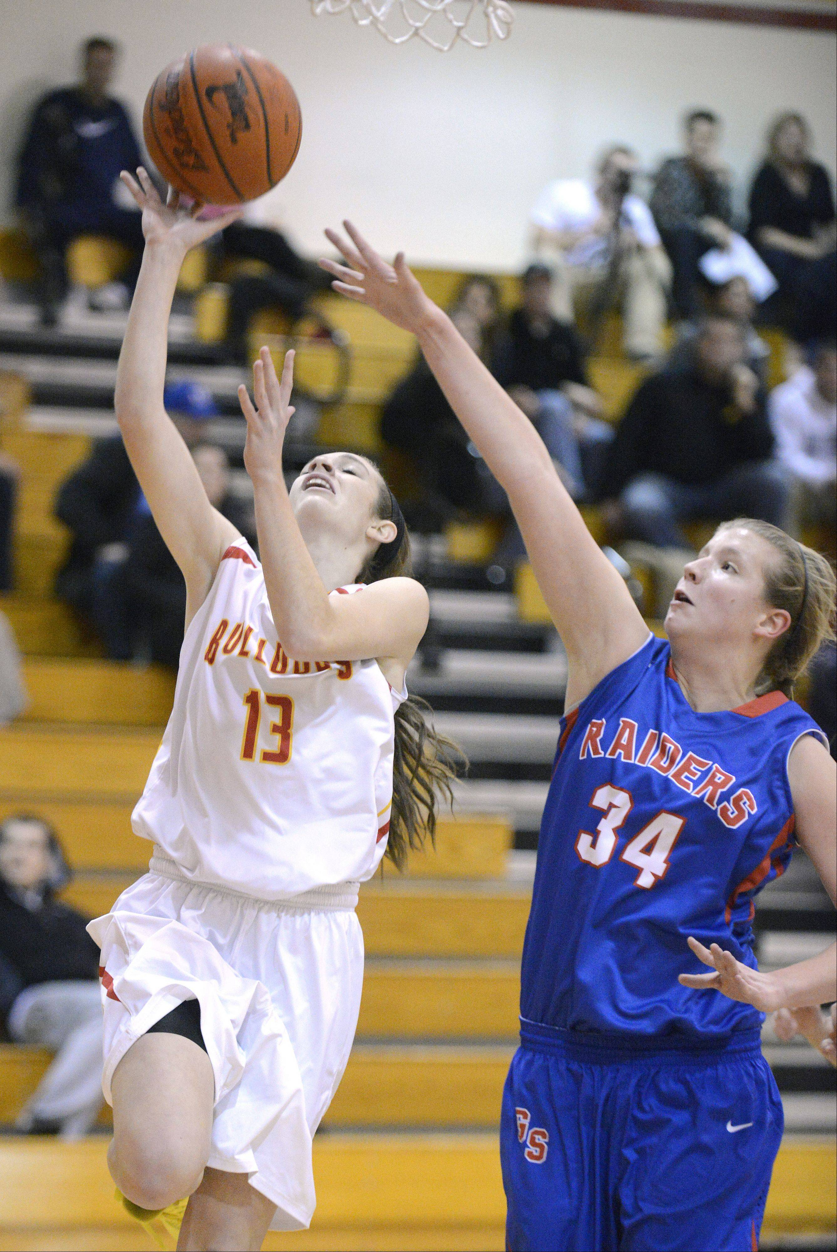 Glenbard South's Sydney Bauman attempts to tip the ball out of the hands of Batavia's Mackenzie Foster as she goes up for the hoop in the first quarter on Tuesday, November 19.
