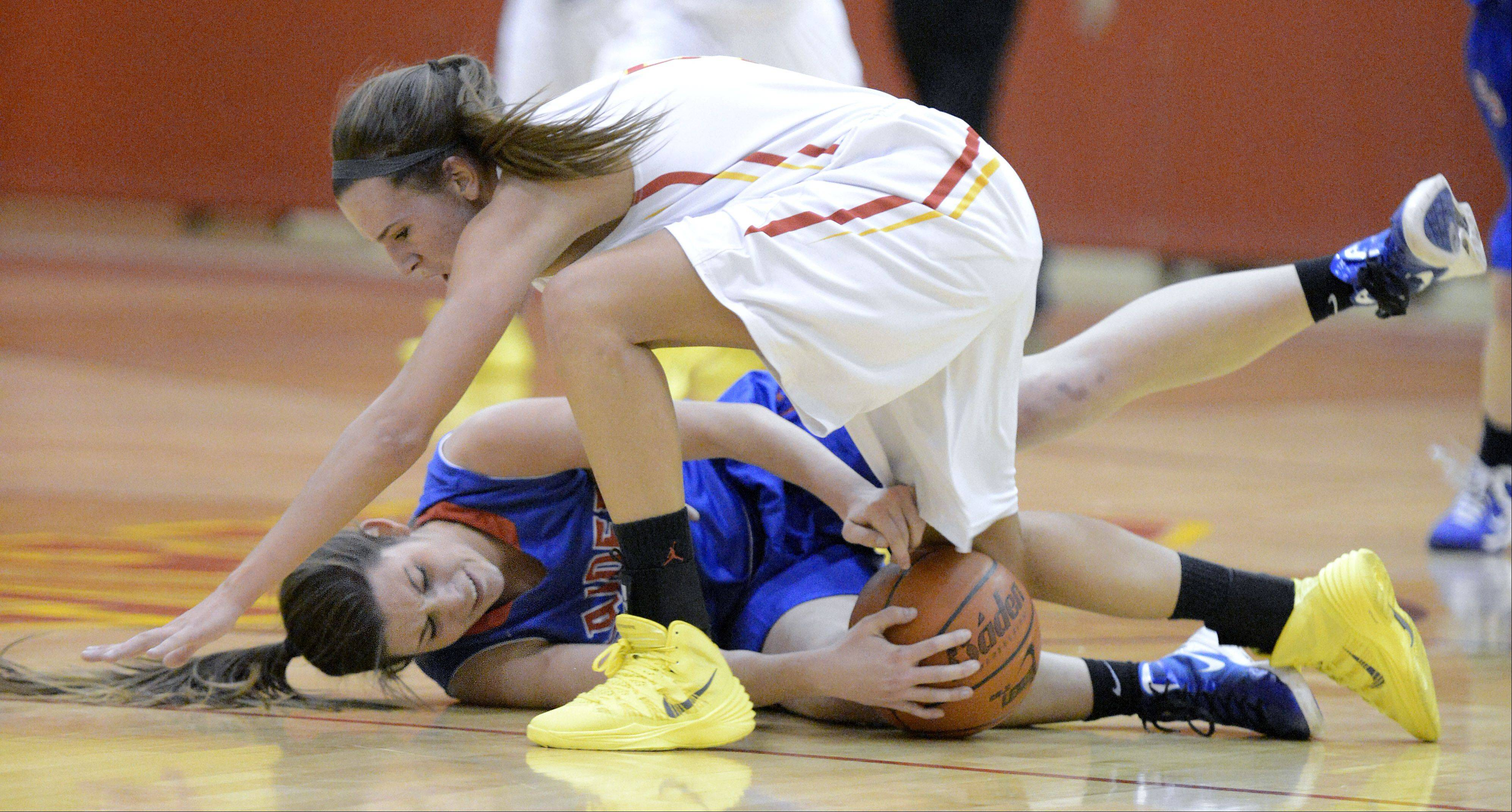 Glenbard South's Alex LaPonte and Batavia's Liza Fruendt go down wrestling for the ball in the first quarter on Tuesday, November 19.