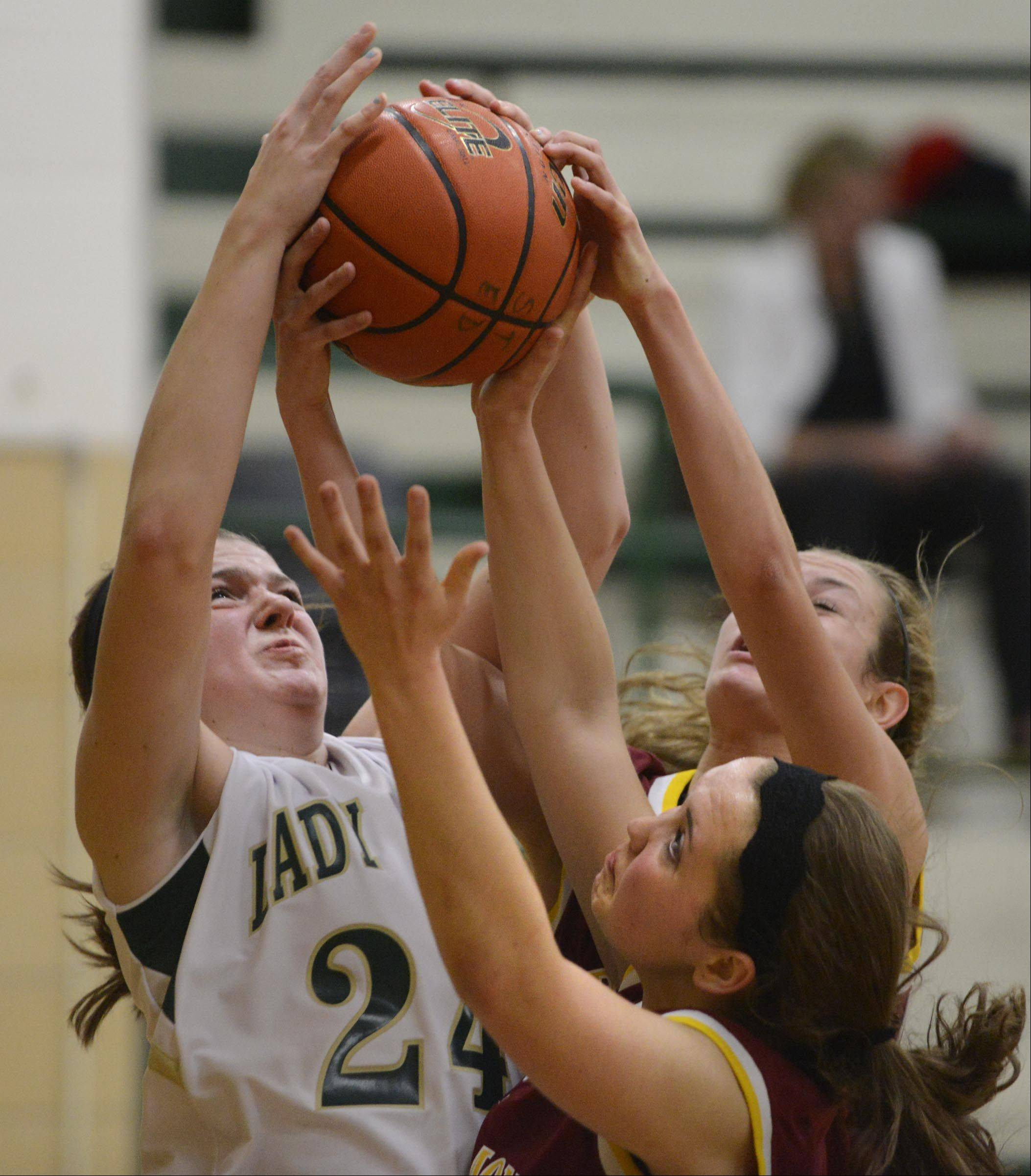St. Edward's Katie Swanson fights for a rebound against Westmont's Rachel Kurt and Annie Carlson Tuesday in Elgin.