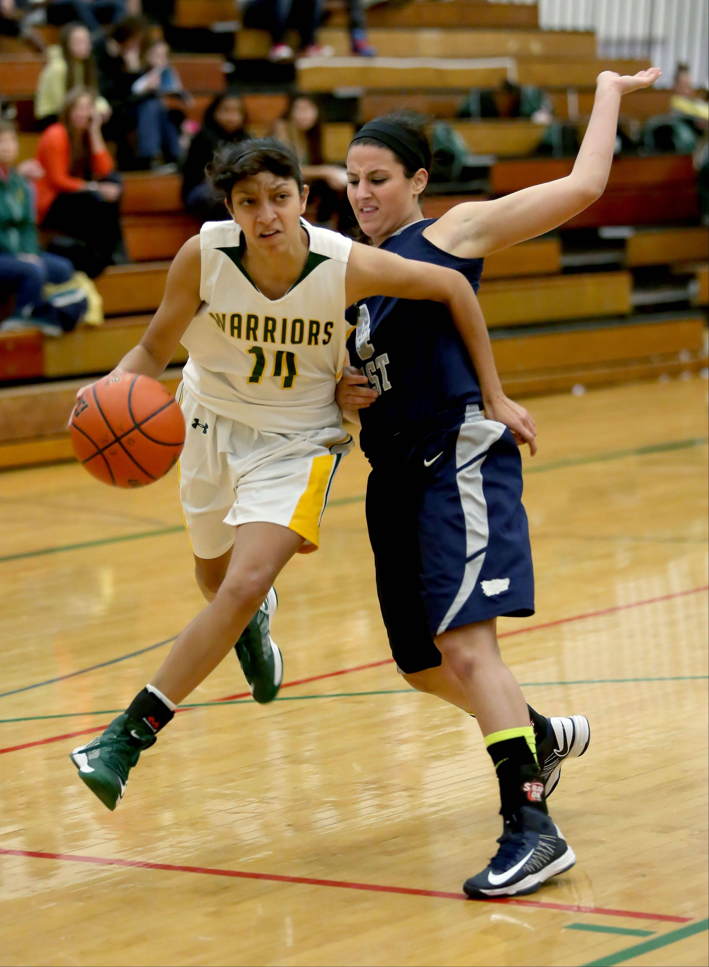 Waubonsie Valley's Andrea Colin drives around Julianna Wadsworth of Oswego East during girls basketball in Aurora on Monday.