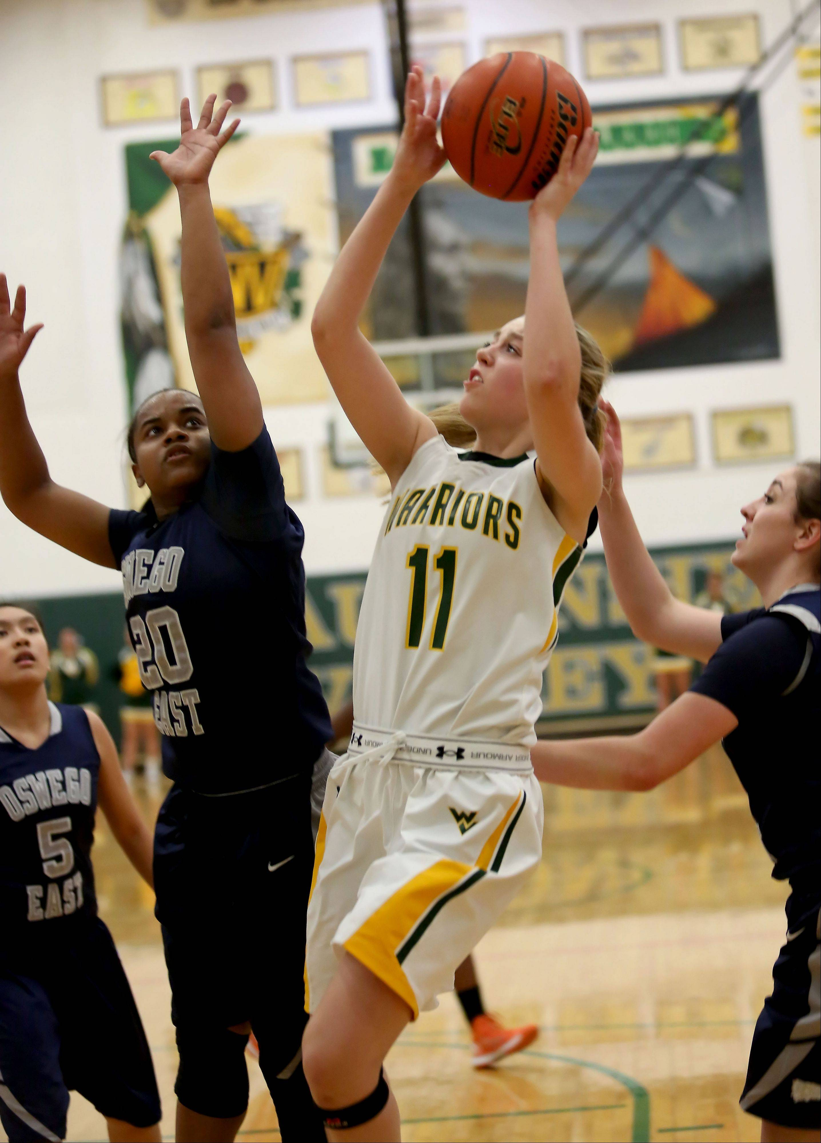 Waubonsie Valley's Katie D'Ouville goes for two points as Venita Parsons of Oswego East defends during girls basketball in Aurora on Monday.