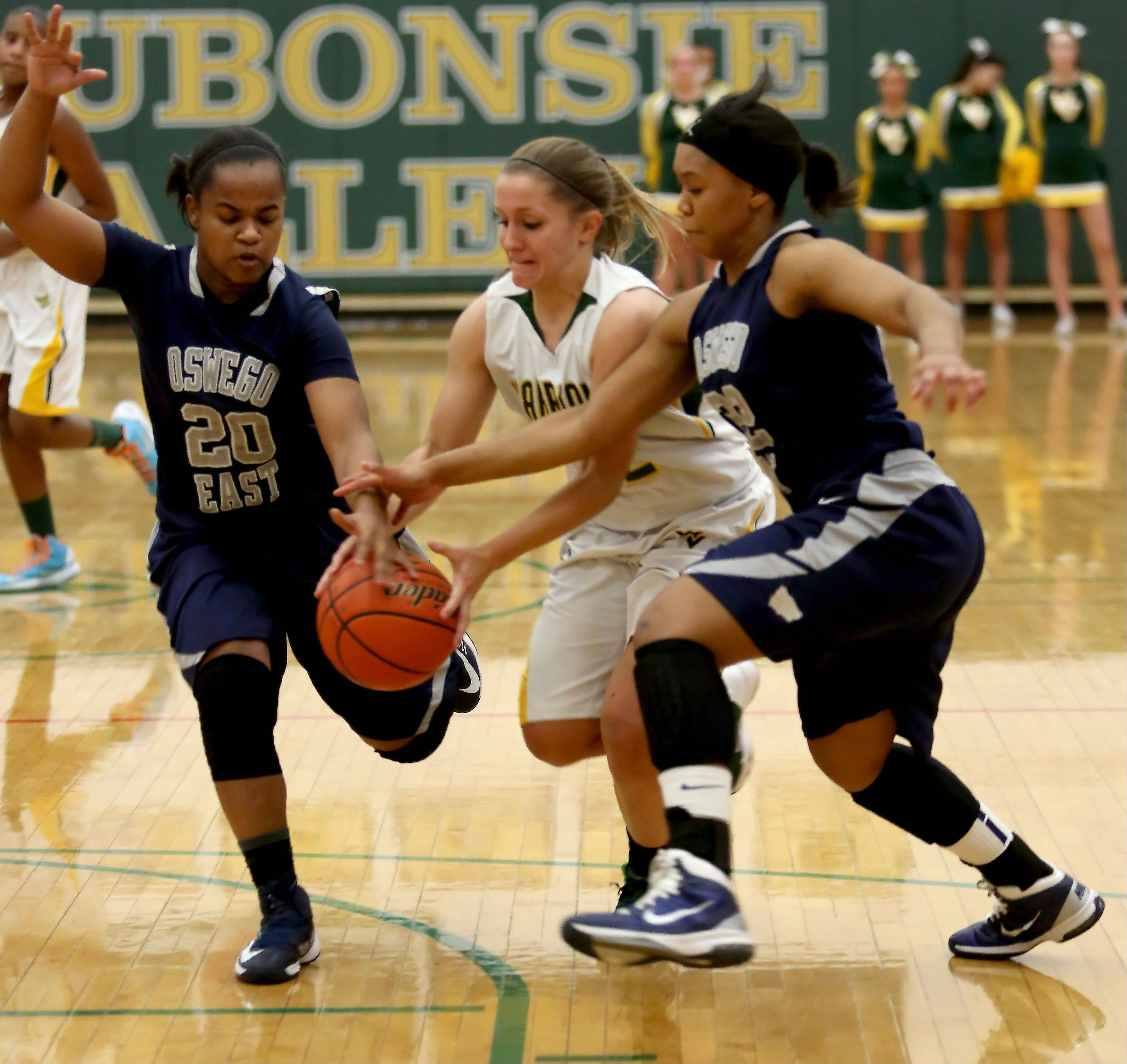 Waubonsie Valley's Emma Rigby goes after a loose ball with Venita Parsons, left and Nia Flowers of Oswego East during girls basketball in Aurora on Monday.