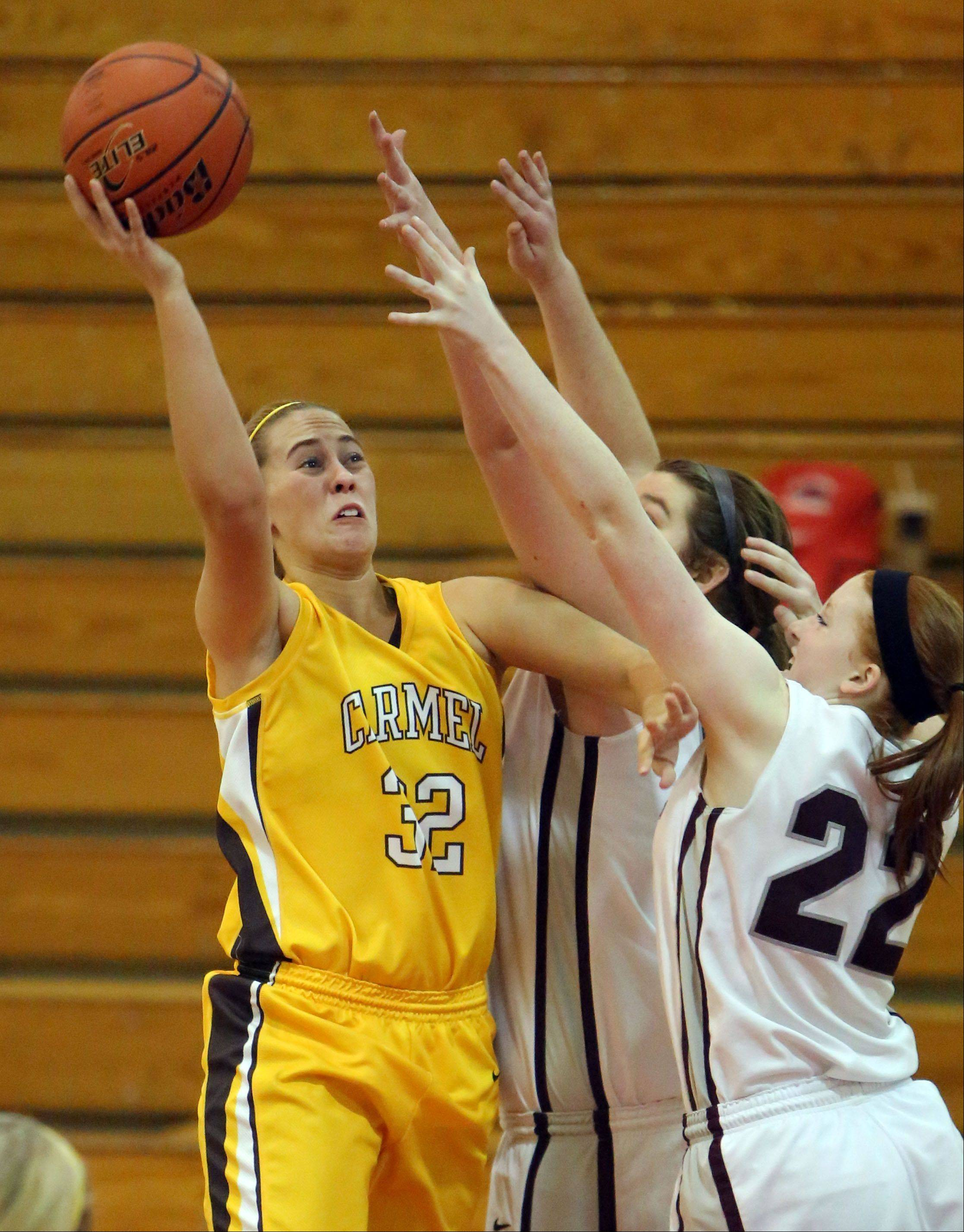 Carmel's Emma Rappe, left, drives on Prairie Ridge's Aly Clark on Wednesday at Mundelein.