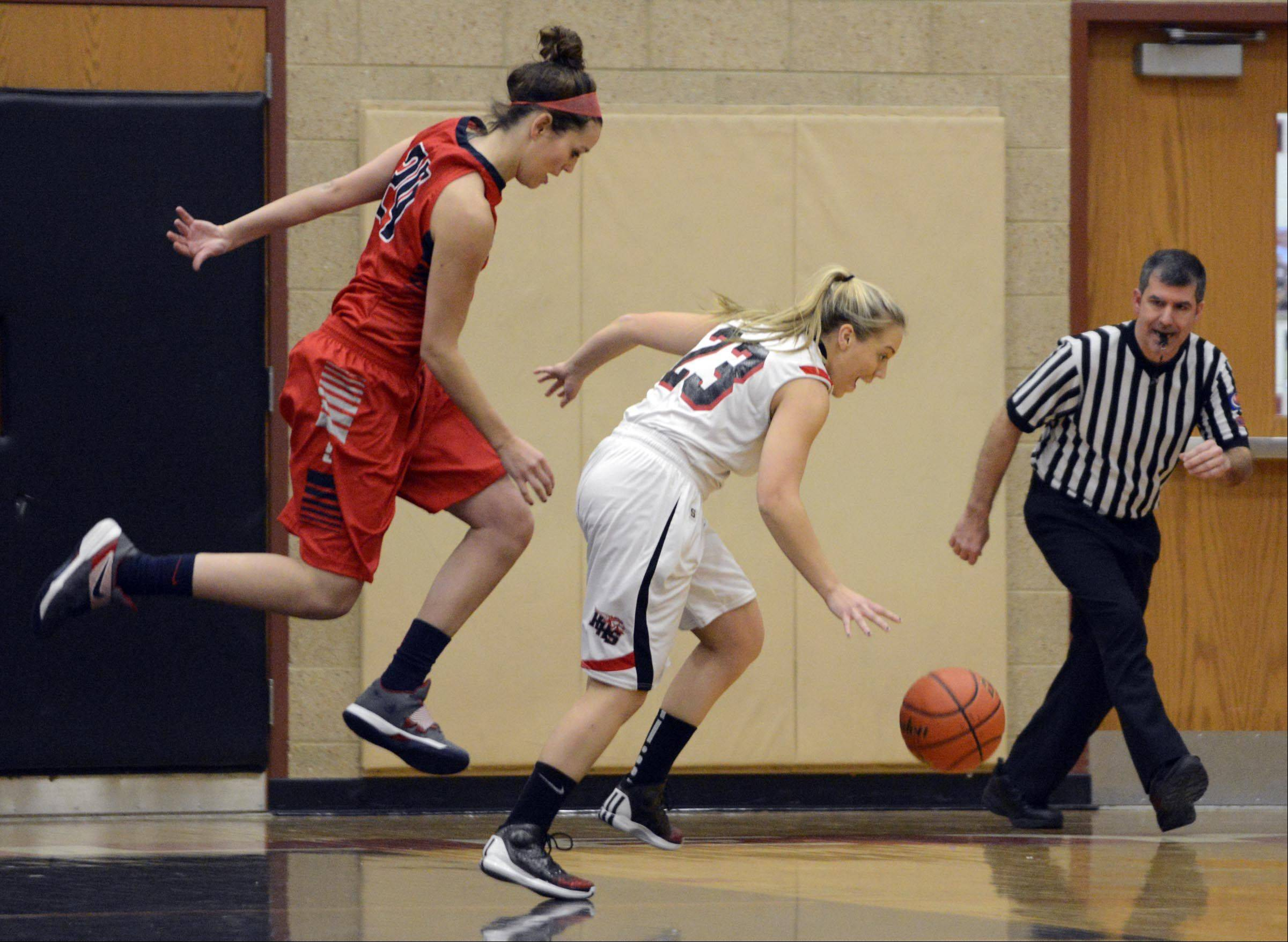 South Elgin's Kennede Miller hops over Huntley's Jessica Brock Wednesday in Huntley.