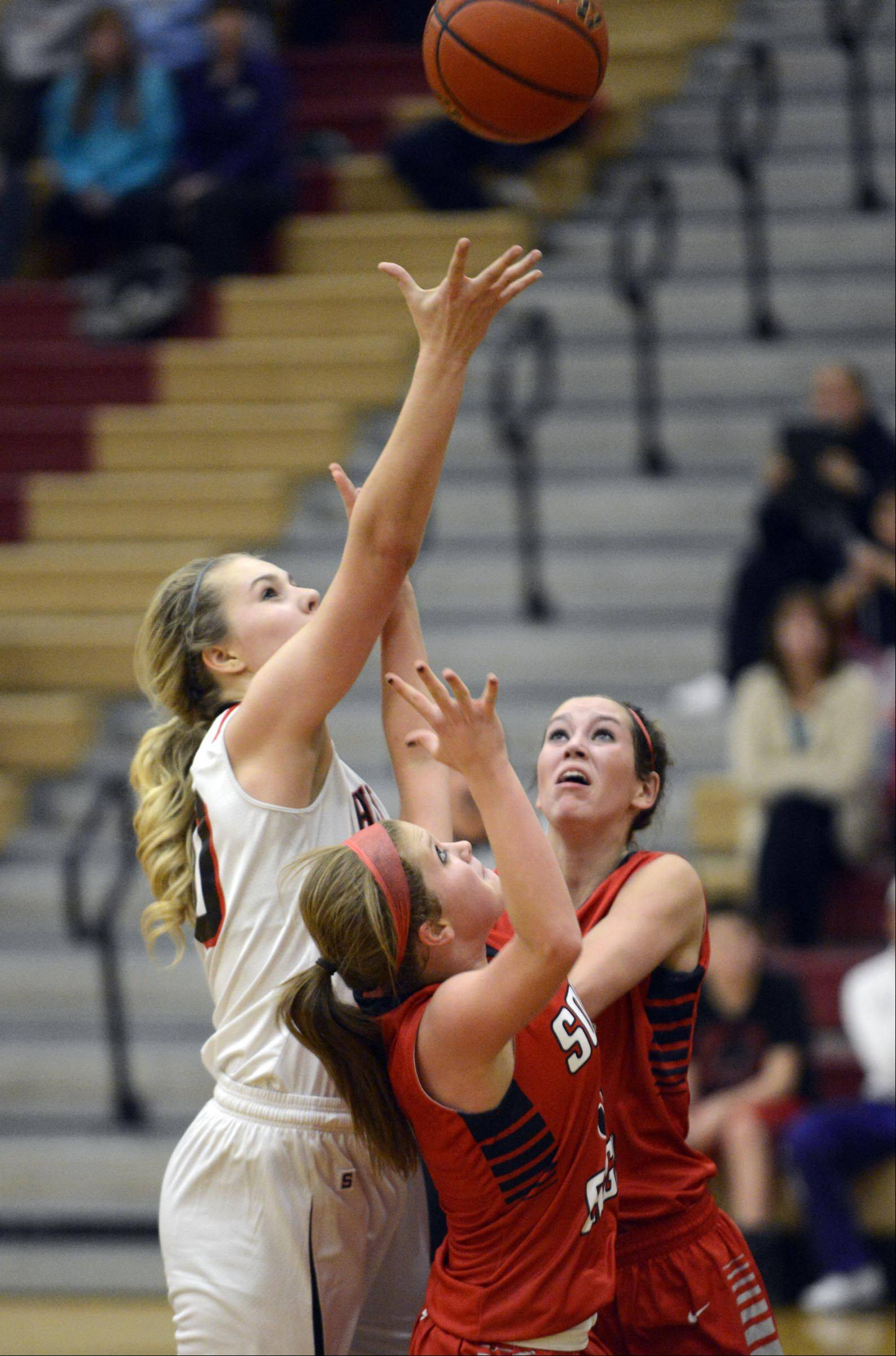 Huntley's Ali Andrews reaches for a rebound over South Elgin's Anna Tracy and Kennede Miller Wednesday in Huntley Andrews was called for a foul on the play.