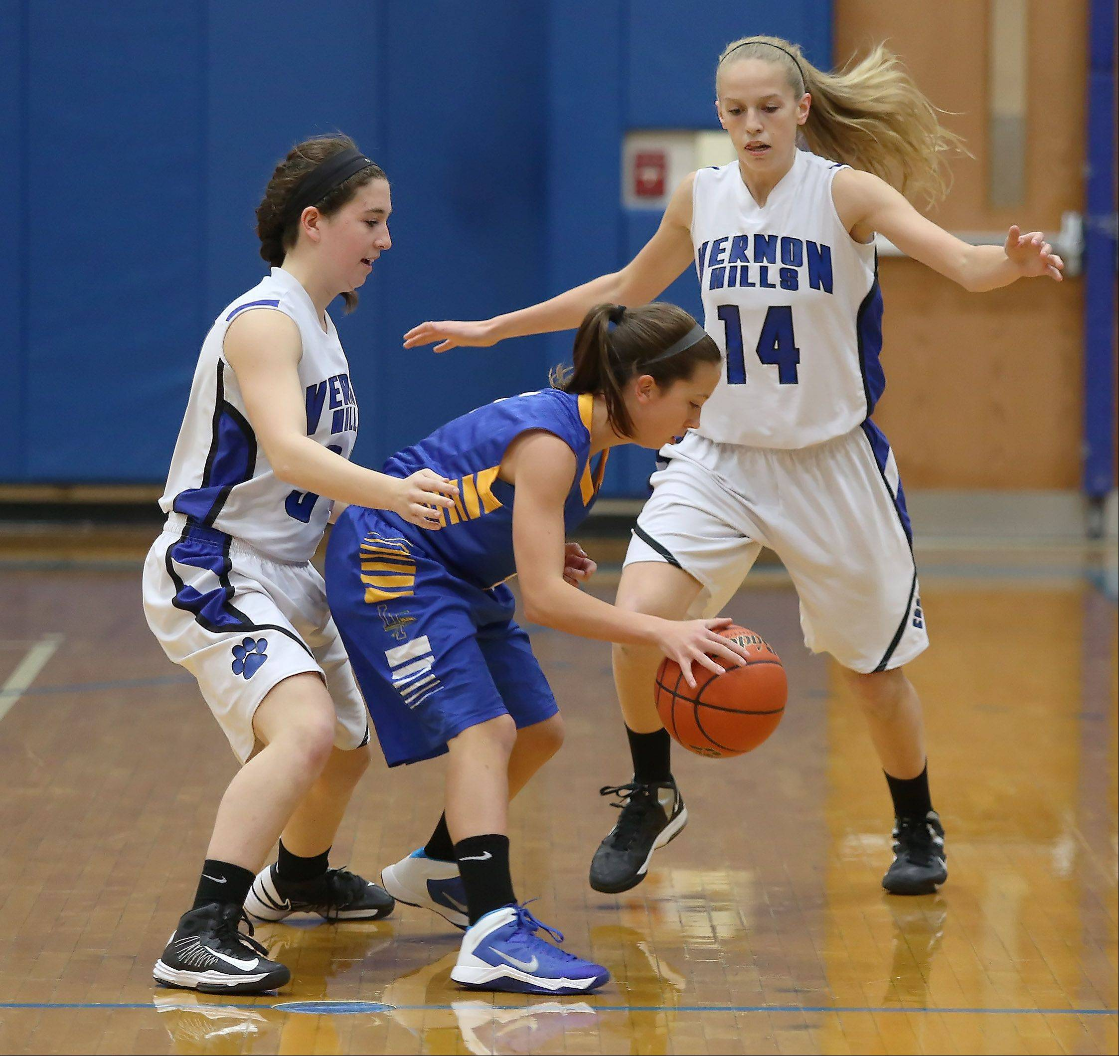 Vernon Hills players Danielle Comitor, left, and Kasey Firnbach trap Lake Forest guard Delaney Williams on Thursday at Vernon Hills.