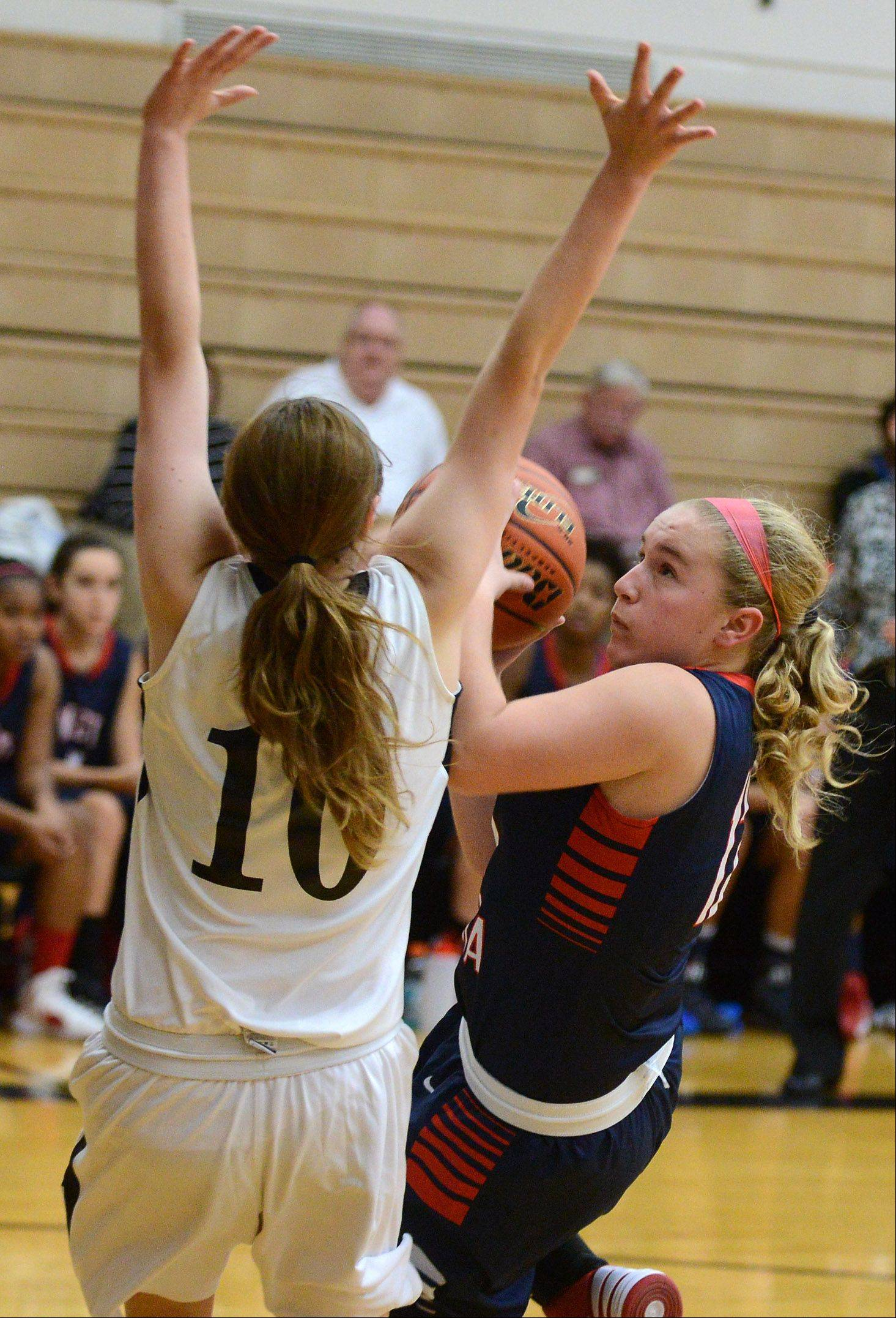 West Aurora's Carley Frauenhoff (12) puts up a shot as she's falling down while defense by Kaneland's Katie Brinkman (10) during Thursday's game in Maple Park.