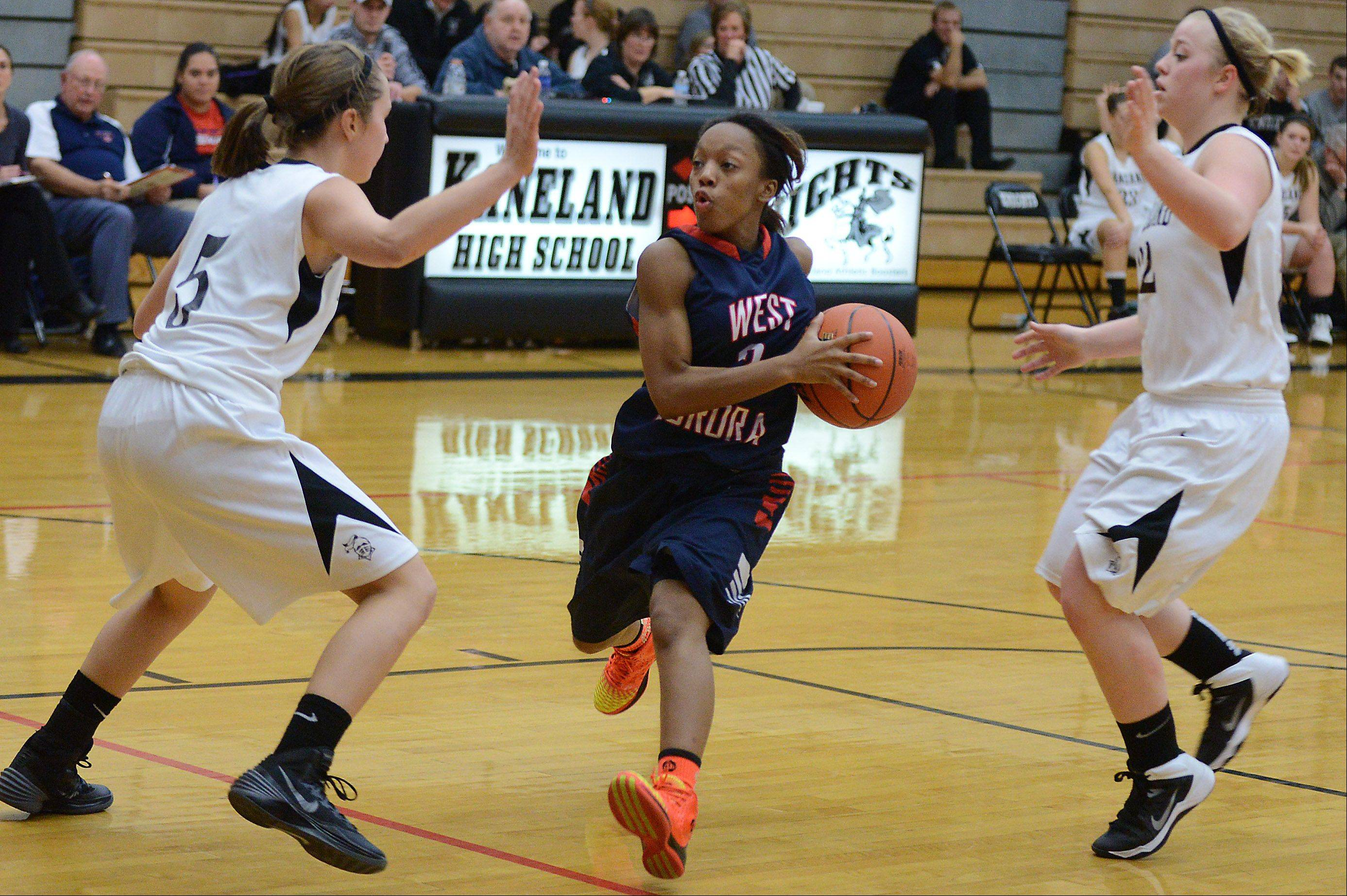 West Aurora's Alexis Wiggins slices through the lane between a pair of Kaneland defenders during Thursday's game in Maple Park.