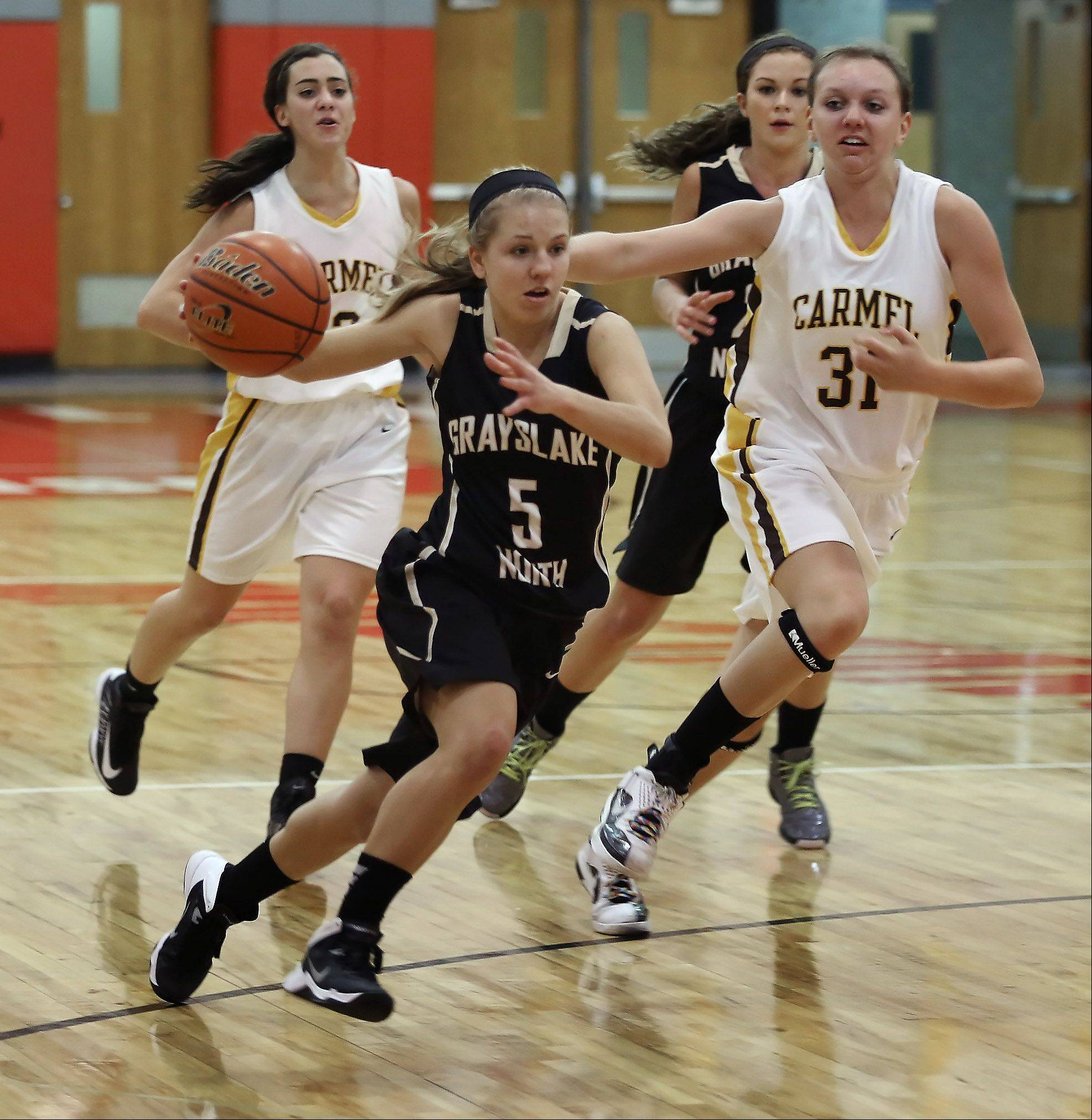 Grayslake North guard Kendall Detweiler races down the court against Carmel Catholic before the end of the third quarter Monday at the Mundelein High School Turkey Tournament. Carmel players Emily Casale, right, and Kathleen Felicelli are following behind.