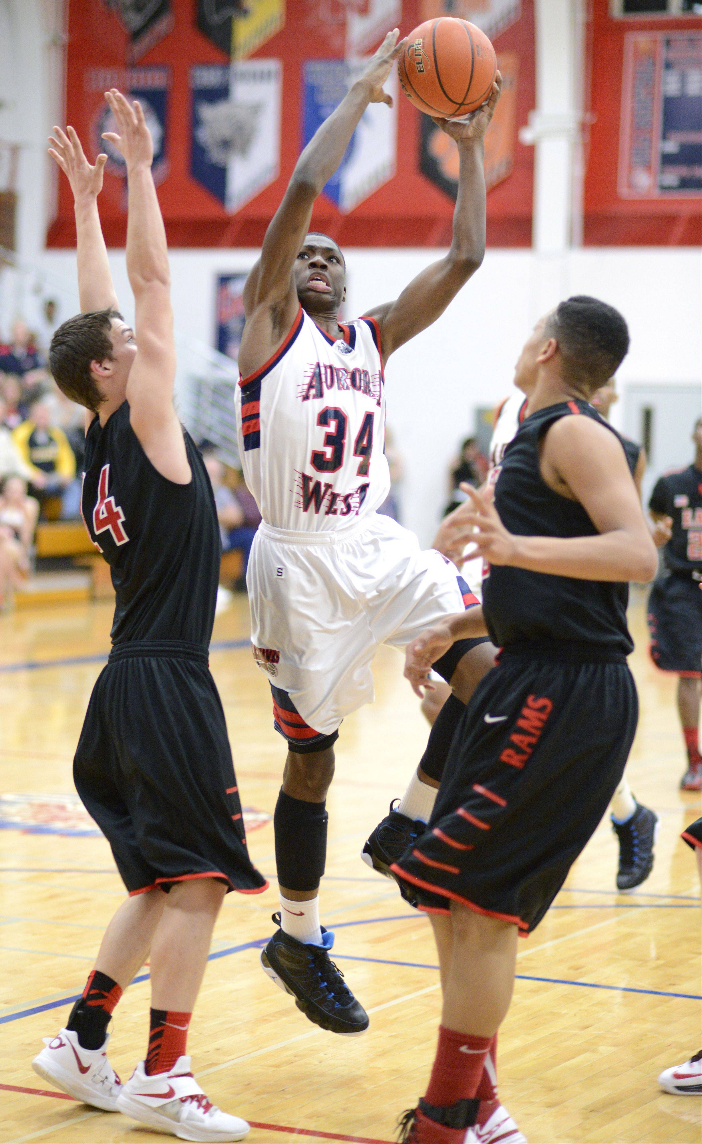 Glenbard East's Mike Kjeldsen and Tahron Harvey attempt a block on West Aurora's Roland Griffin in the second quarter on Wednesday, February 20.