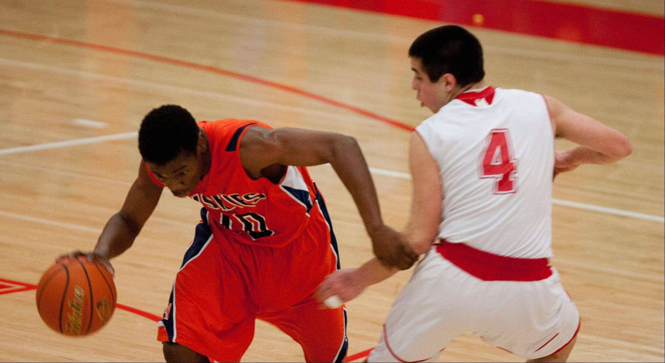 Daniel White/dwhite@dailyherald.com ¬ Naperville North's Jelani McClain Jr., left, runs the offense as Naperville Central's Ryan Anthony (4), defends, during boys basketball action at Naperville Central High School.