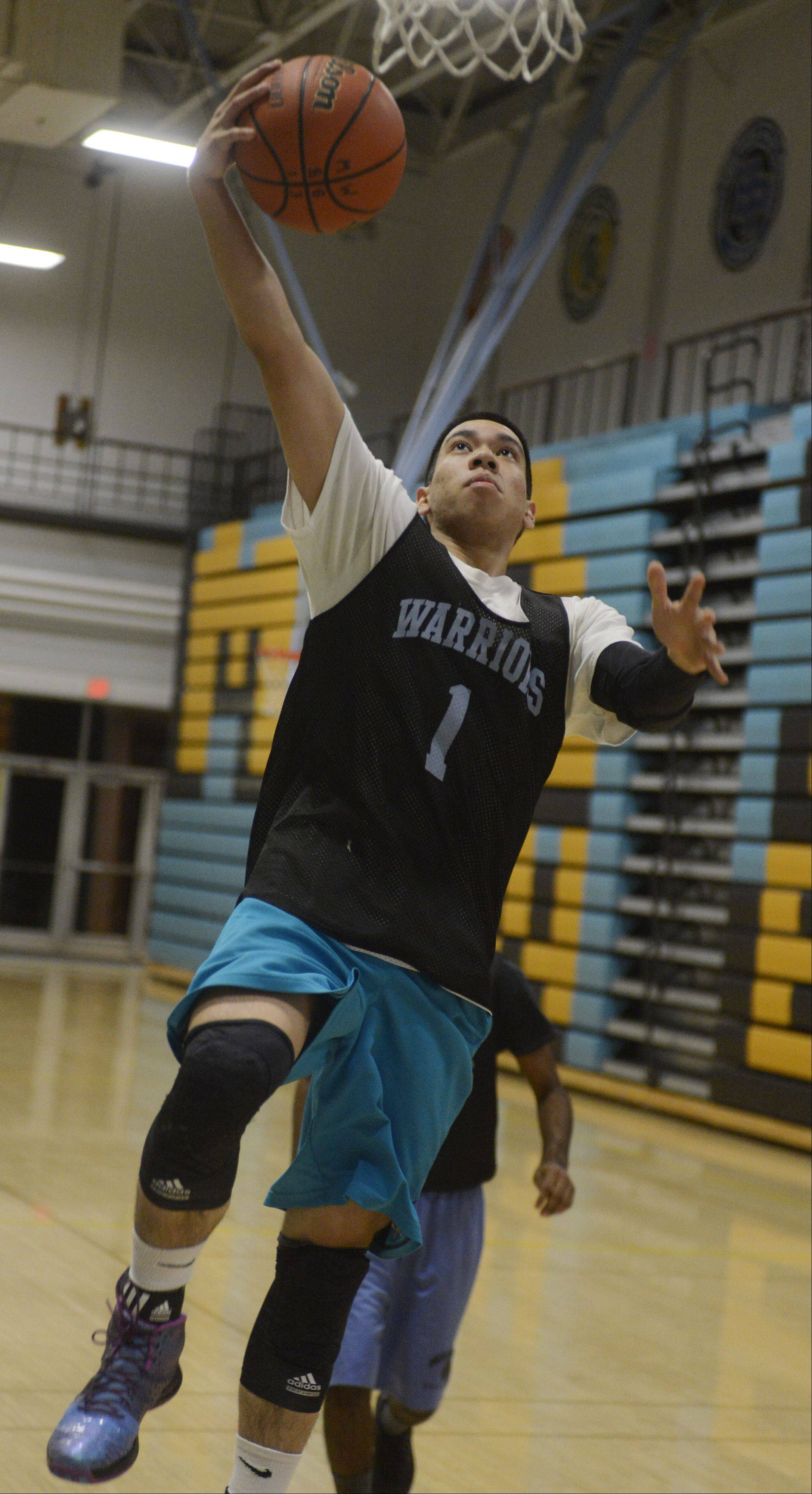 Maine West's Joel Ferraren drives to the basket during practice.