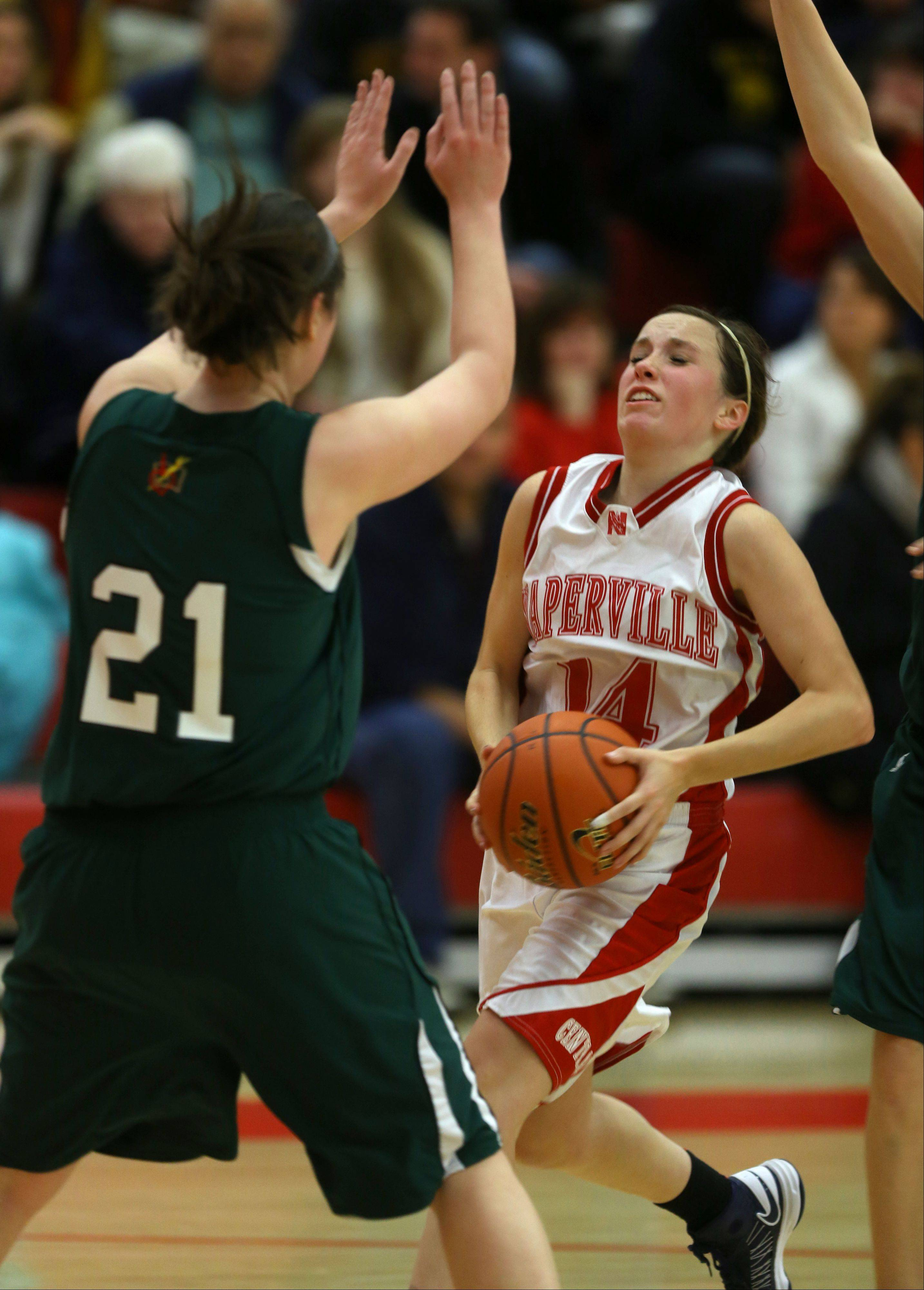 Naperville Central's Emily Kraft drives the lane against Providence's Mary Fashingbauer (21), during the 2013 girls basketball Tip-Off Tournament.