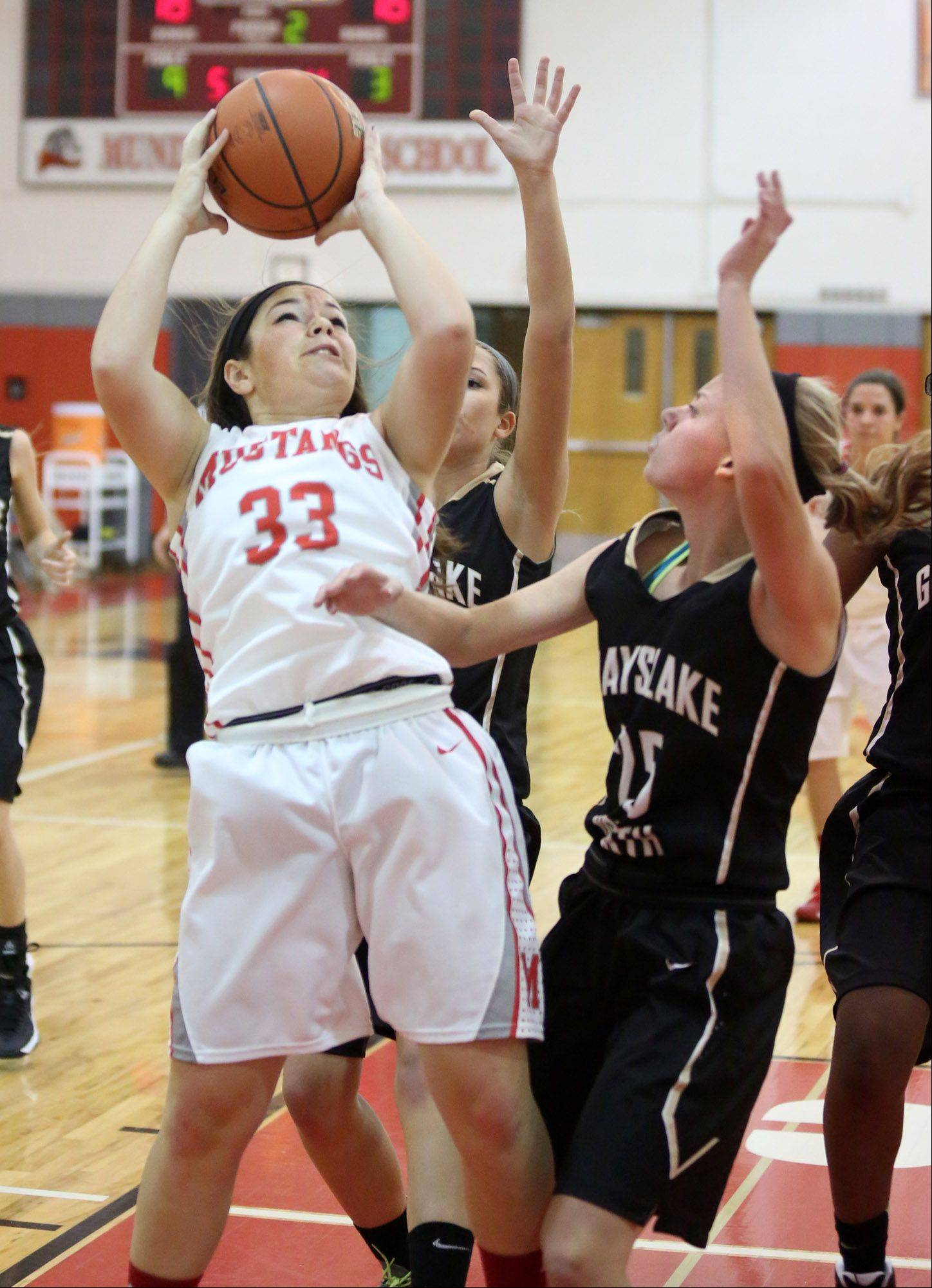Mundelein guard Maria DeVito shoots over Grayslake North defender Samantha Villwock at Mundelein Mustangs on Friday.