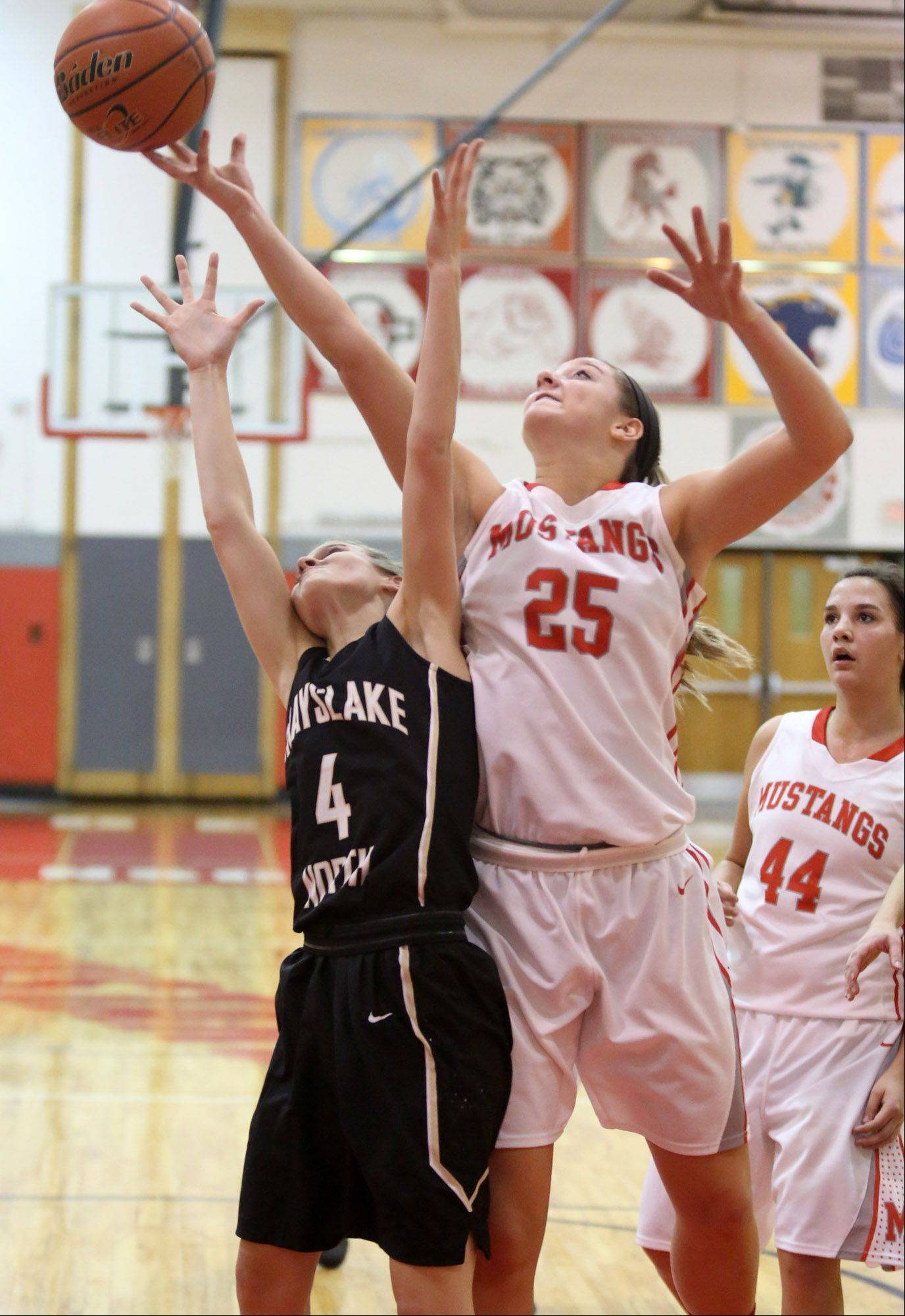 Mundelein's Jamie Hemmer and Grayslake North's Maggie Fish reach for a rebound at Mundelein on Friday.