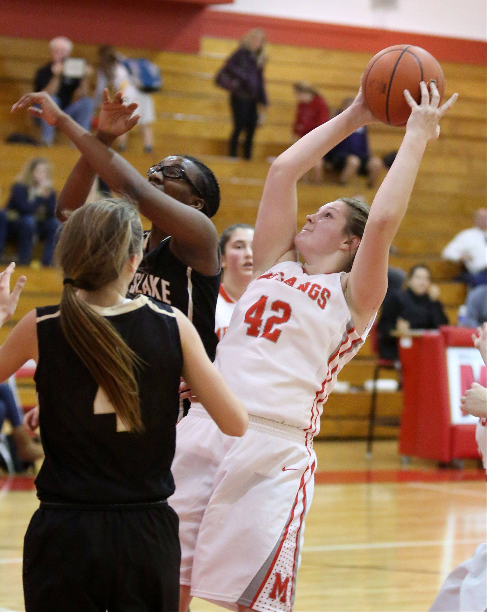 Mundelein's Taylor Lintner pulls in an offensive rebound and shoots against Grayslake North's Brittney Thibeaux, background, at Mundelein on Friday.
