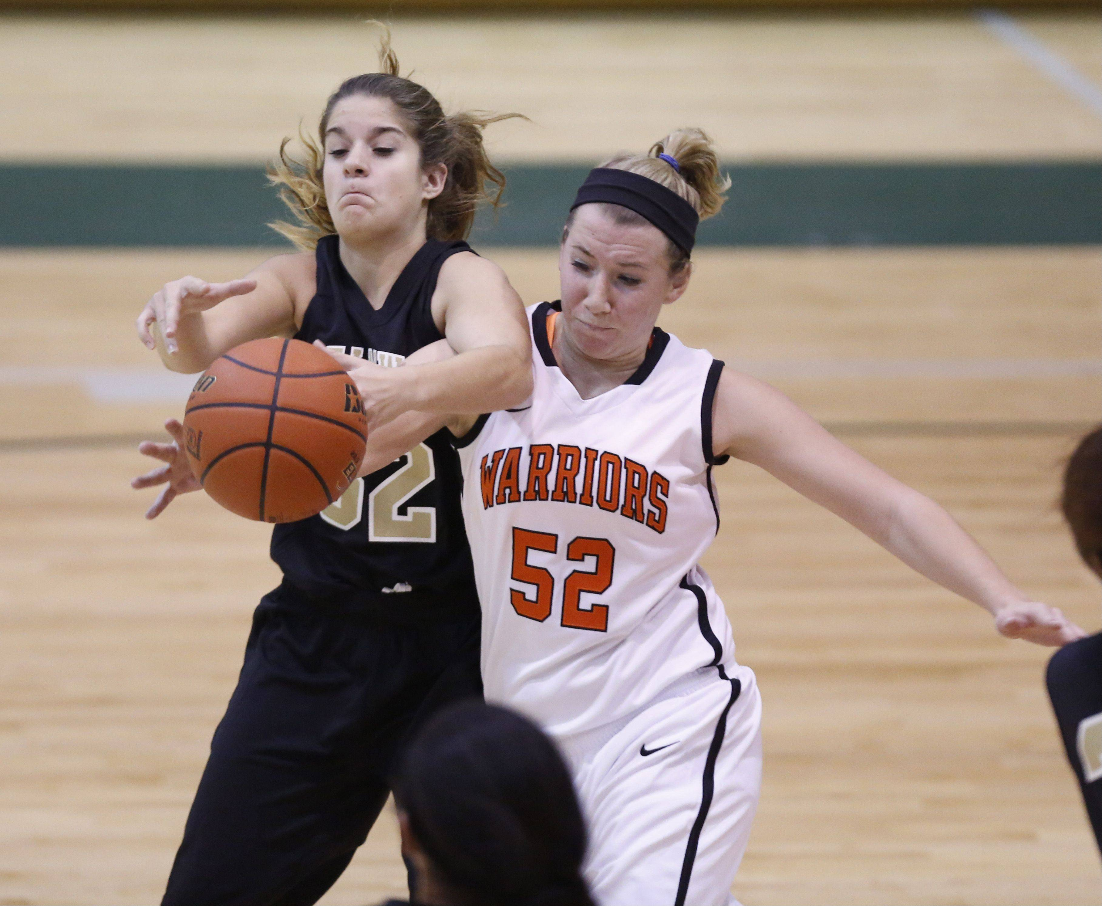 Streamwood's Rachel Clark (32) battles McHenry's Sawyer Lay for a loose ball Friday.