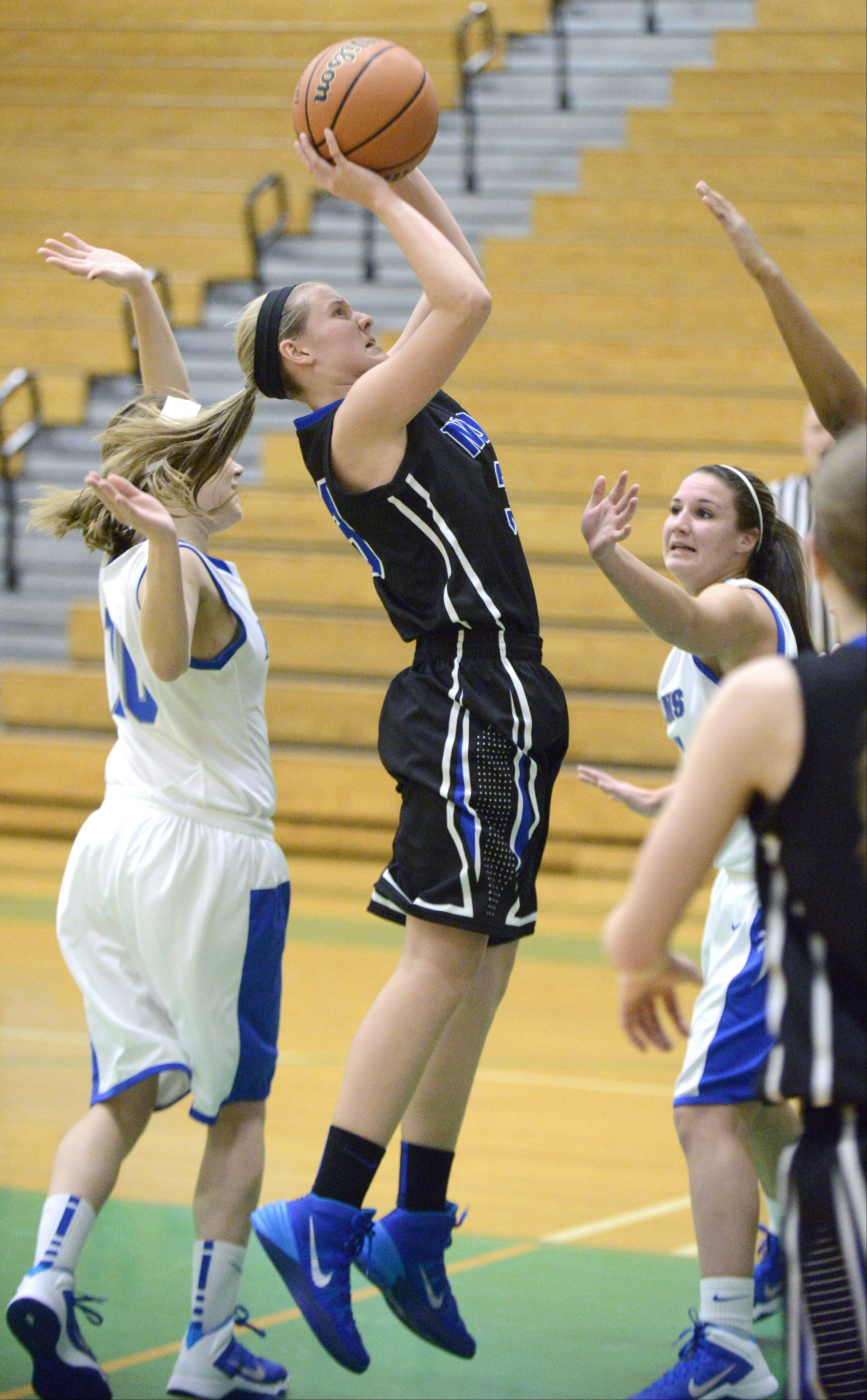 St. Charles North's Nicole Davidson shoots over a Wheaton North blockade in the first quarter on Friday, November 22.