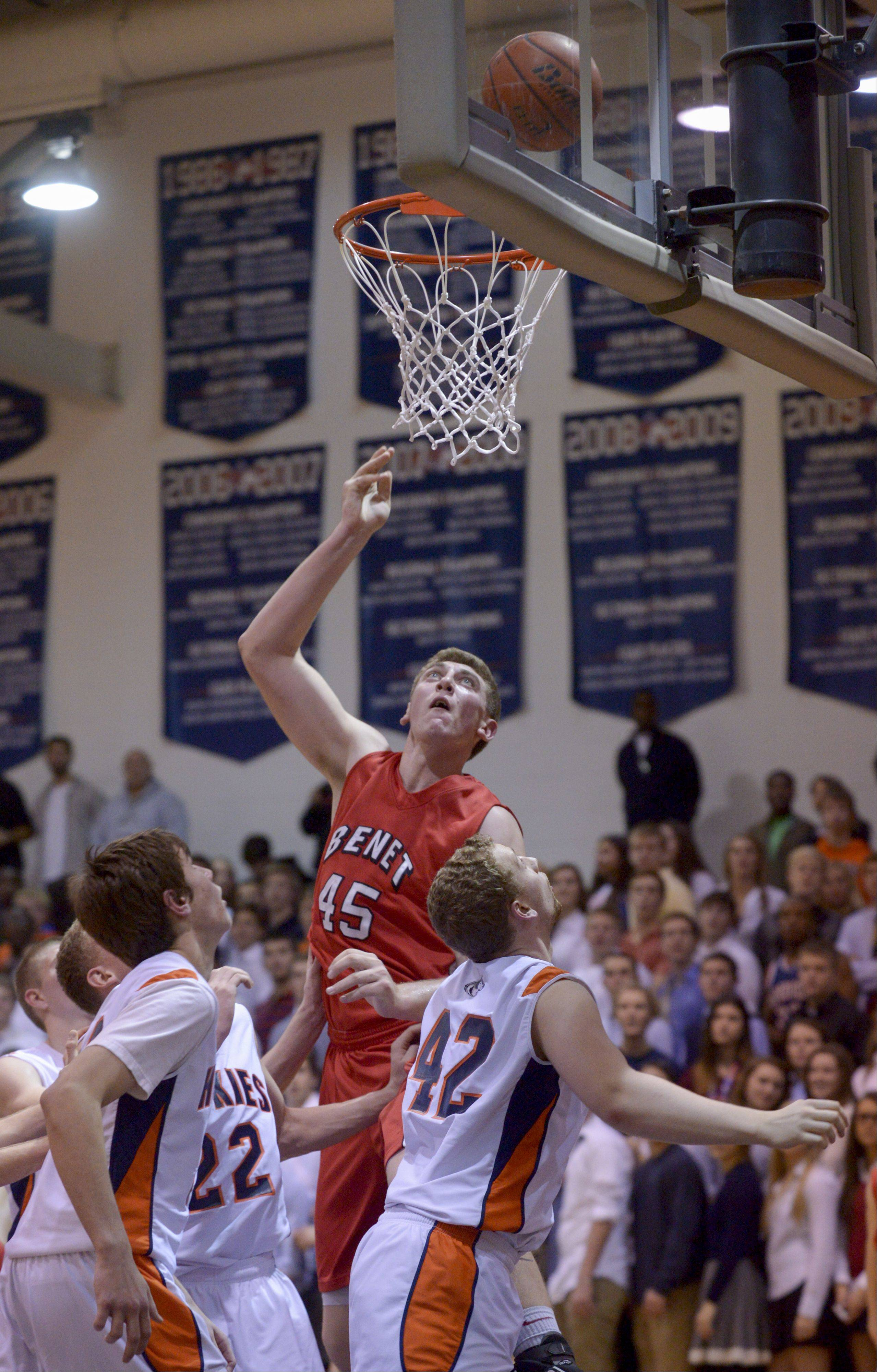 Benet's Sean O'Mara takes a shot over Naperville North defenders, during in boys basketball in Naperville Sunday.