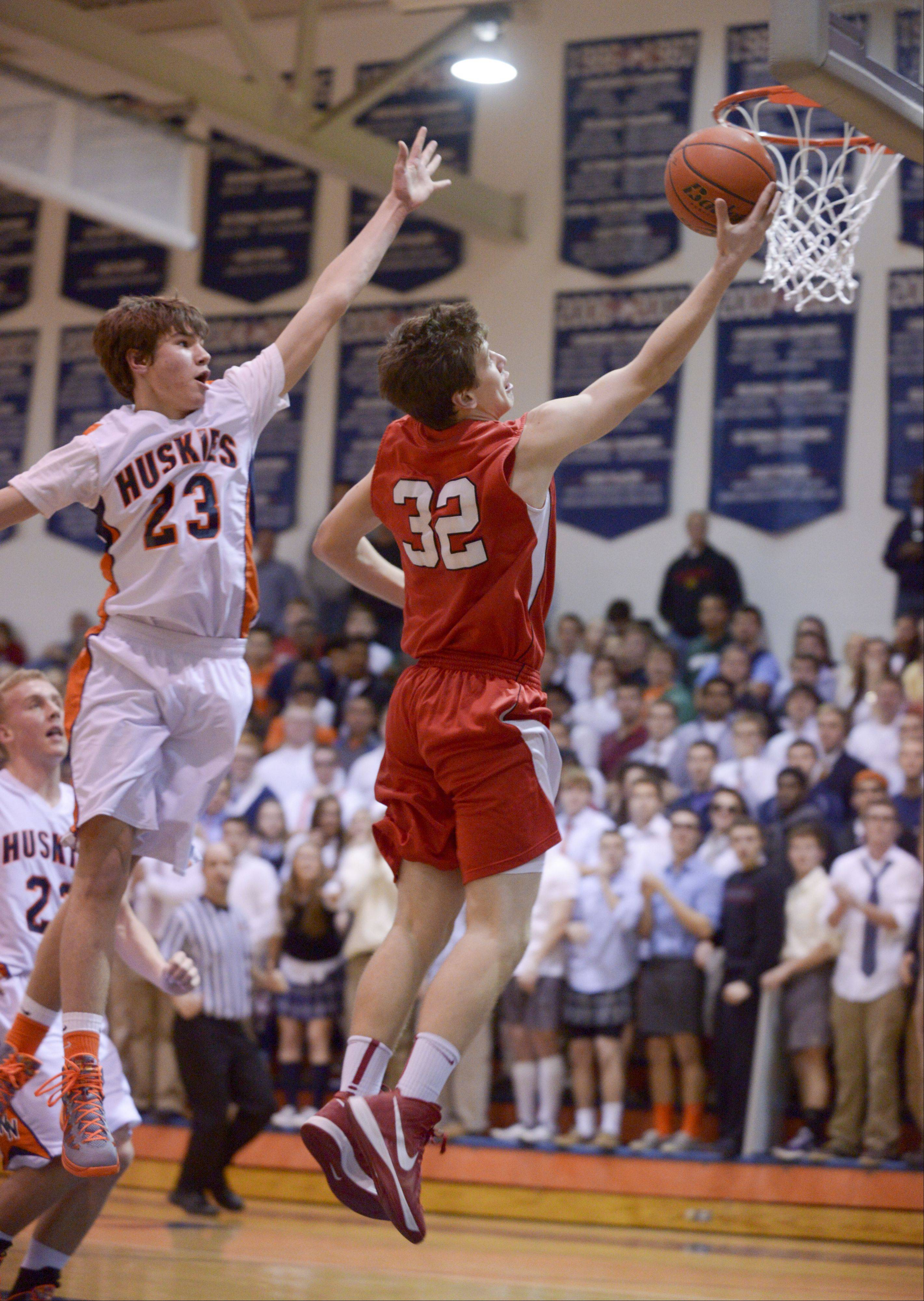 Benet's Dan Sobolewski lays up for a shot getting past Naperville North's Mitch Lewis, during in boys basketball in Naperville Sunday.