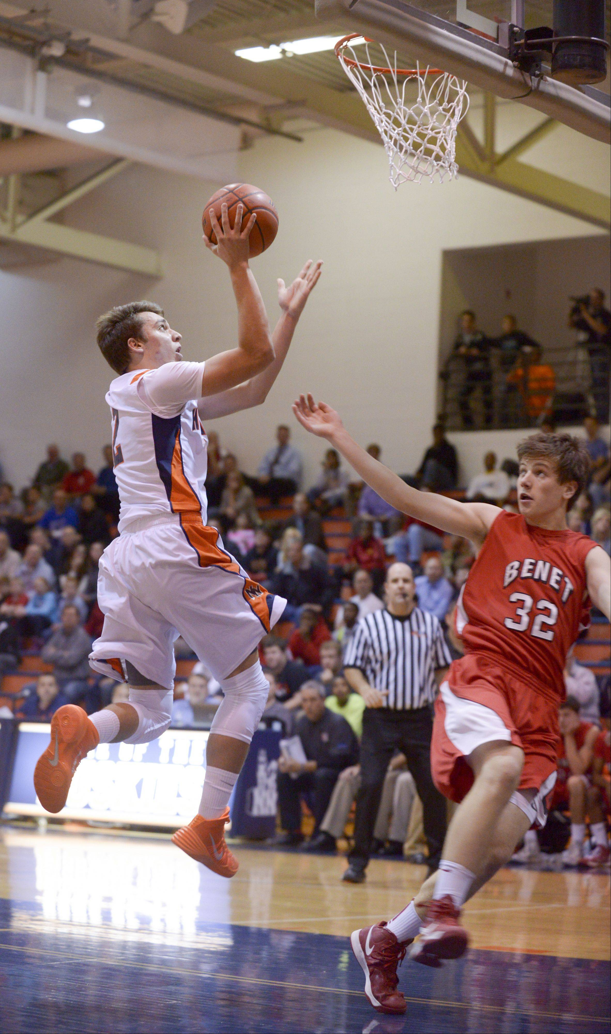 Naperville North's Anthony Rehayem takes a shot as Benet's Dan Sobolewski looks on, during in boys basketball in Naperville Sunday.