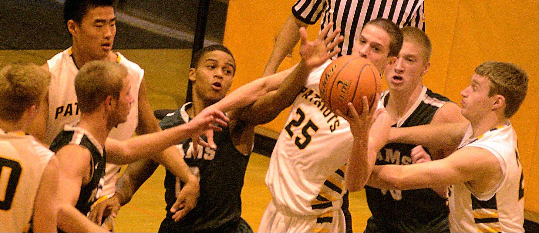 Grayslake Central's Malcolm Reed, center left, and Stevenson's Jordan Hodes, center right, are at the center of a rebound tussle at Buffalo Grove High School on Monday evening.