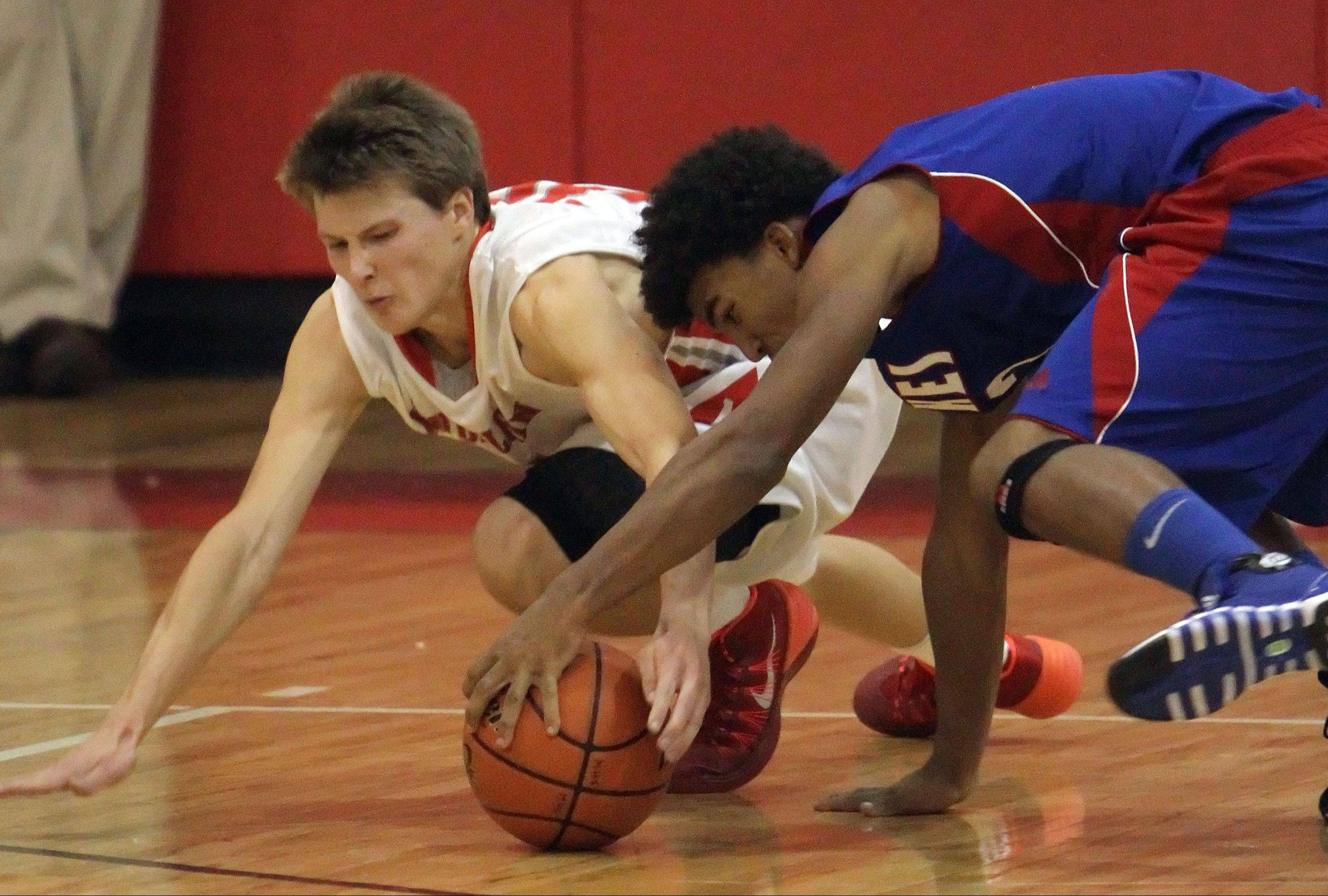 Mundelein's J.T Michalski, left, Lakes' Devyn Cedzidlo scramble for a loose ball Tuesday at Mundelein.