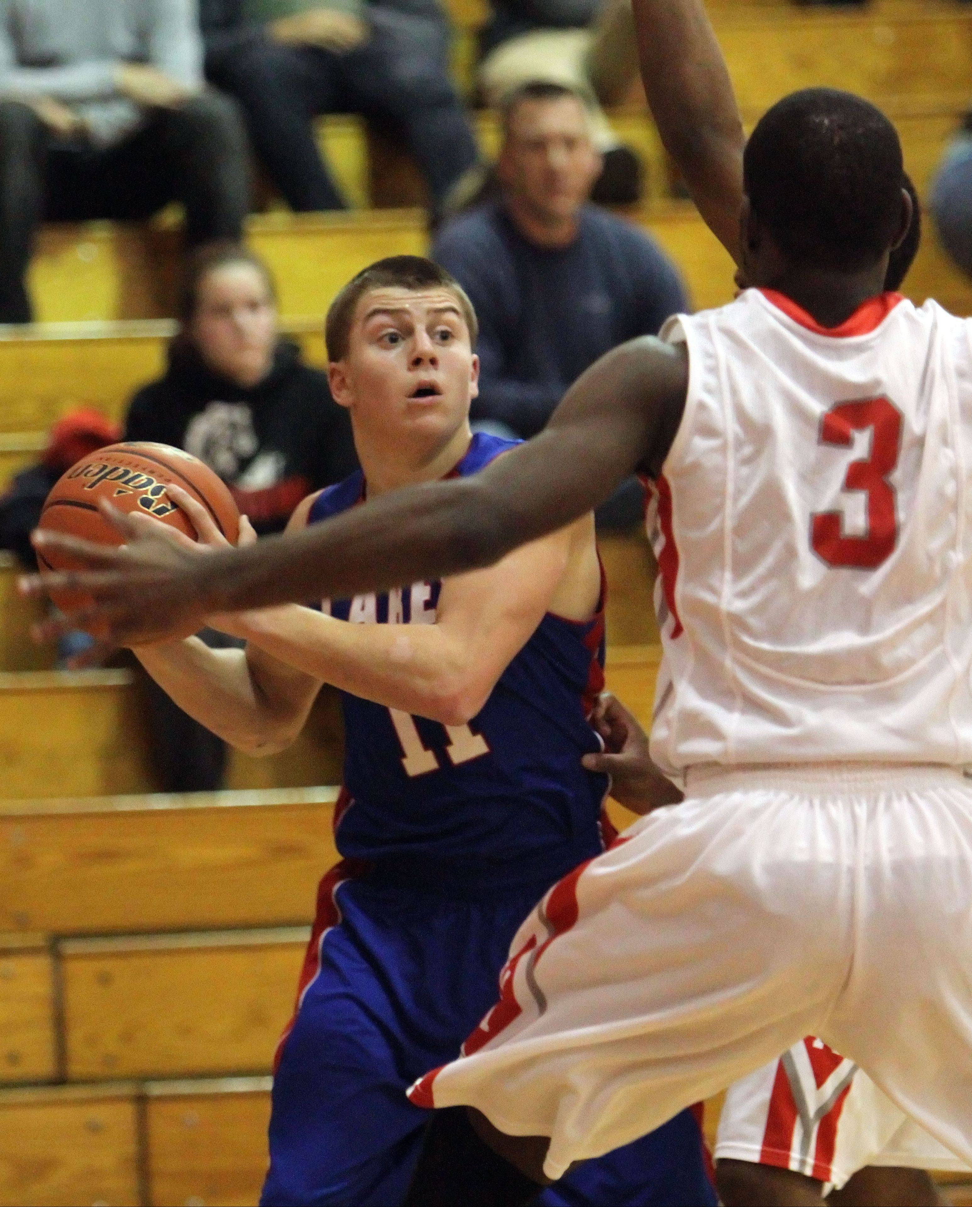 Lakes' Jacob Balliu, left, looks to pass around Mundelein's Nate Williams on Tuesday at Mundelein.