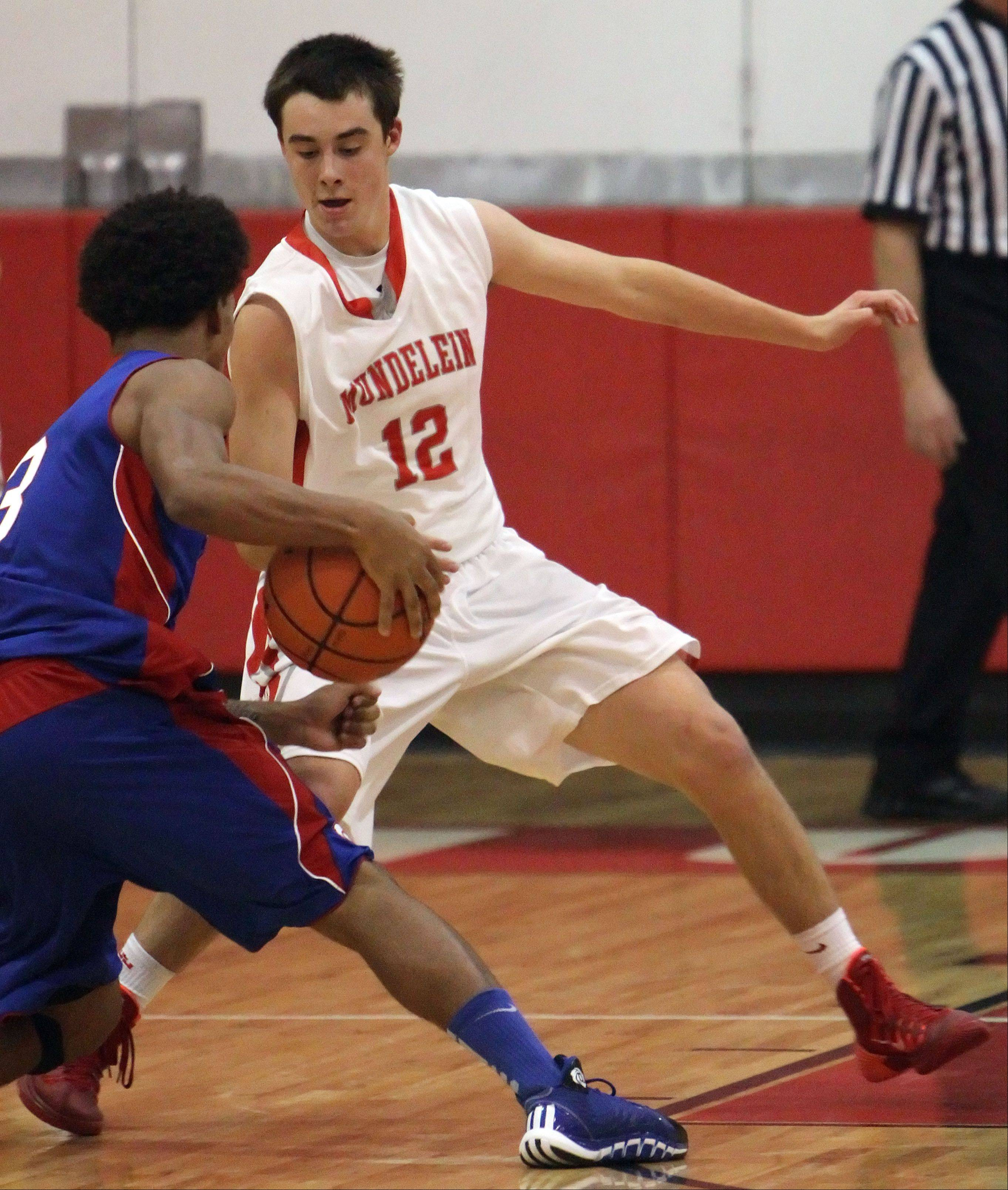 Mundelein's Derek Parola, defends against Lakes' Devyn Cedzidlo on Tuesday at Mundelein.