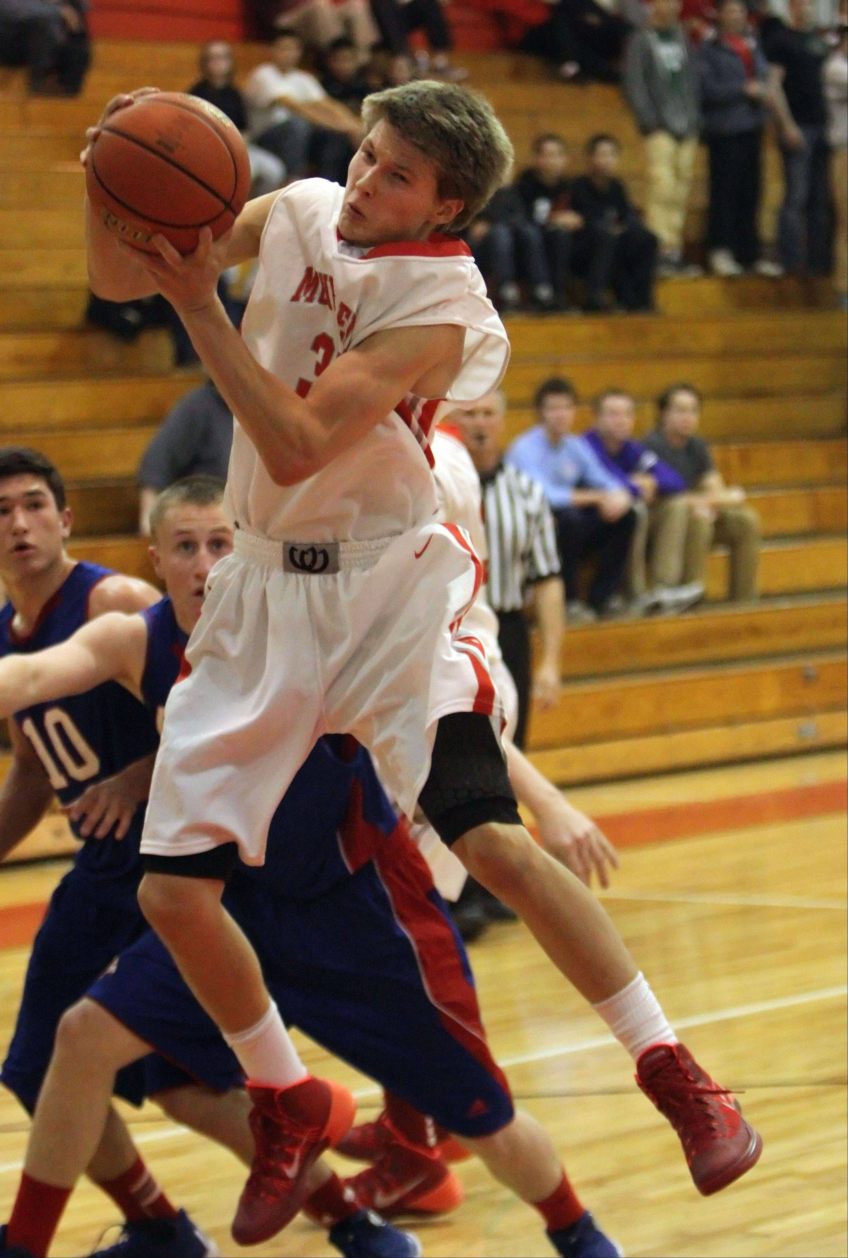 Mundelein's J.T Michalski pulls down a rebound against Lakes on Tuesday at Mundelein.