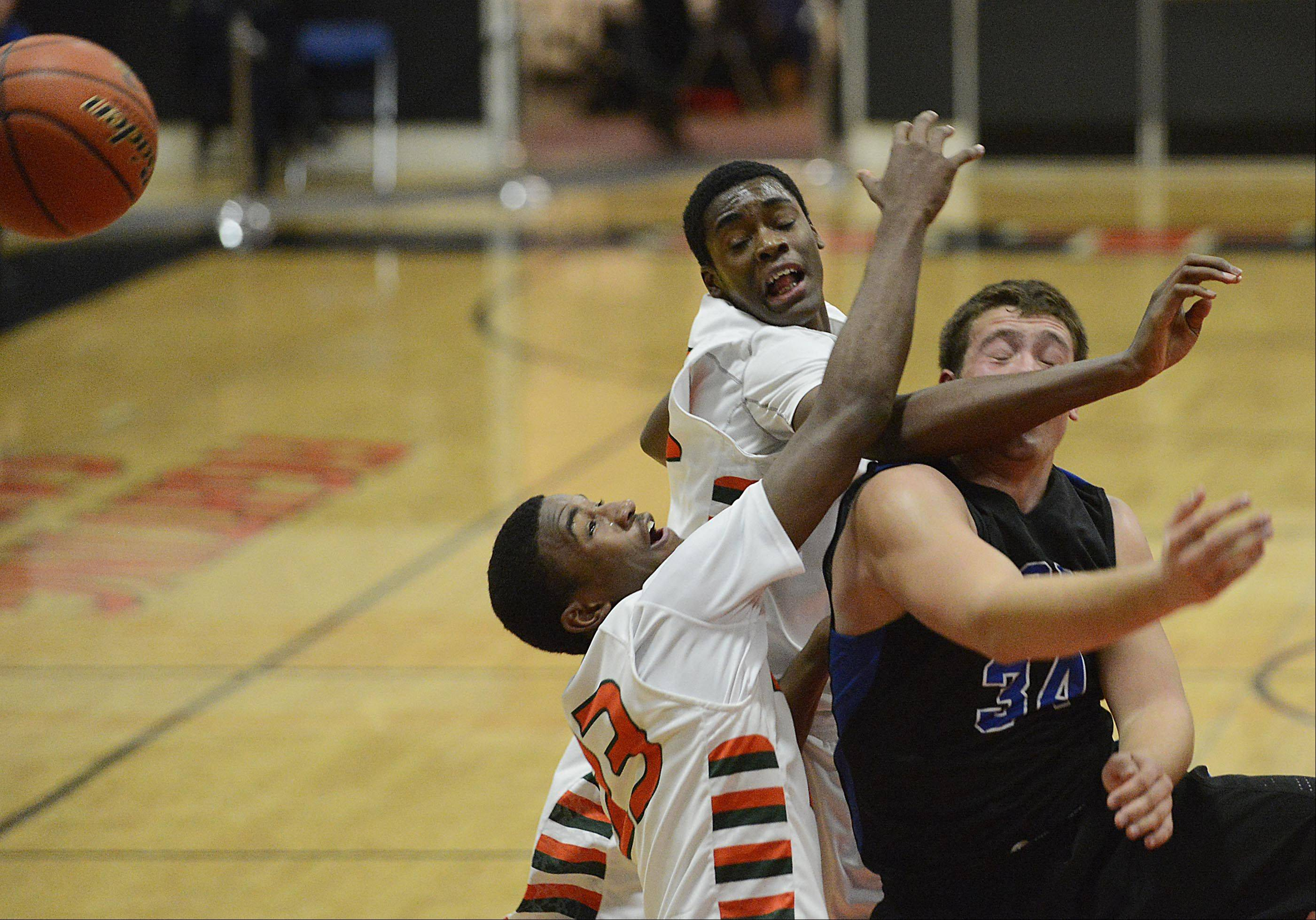 St. Charles North's Garrett Johnson and Plainfield East's Aaron Jordan and James Claar tangle Tuesday in St. Charles.