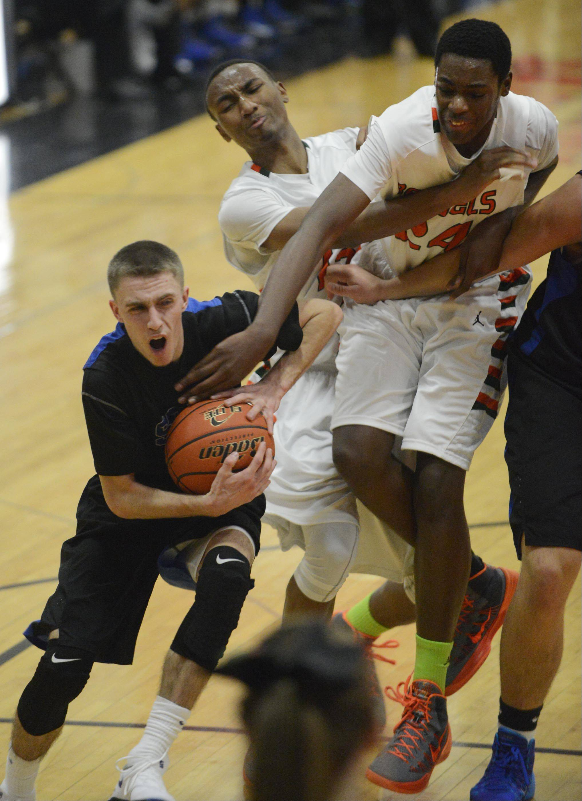 St. Charles North's Alec Goetz drives around Plainfield East's Myles Ward and James Claar Tuesday in St. Charles.