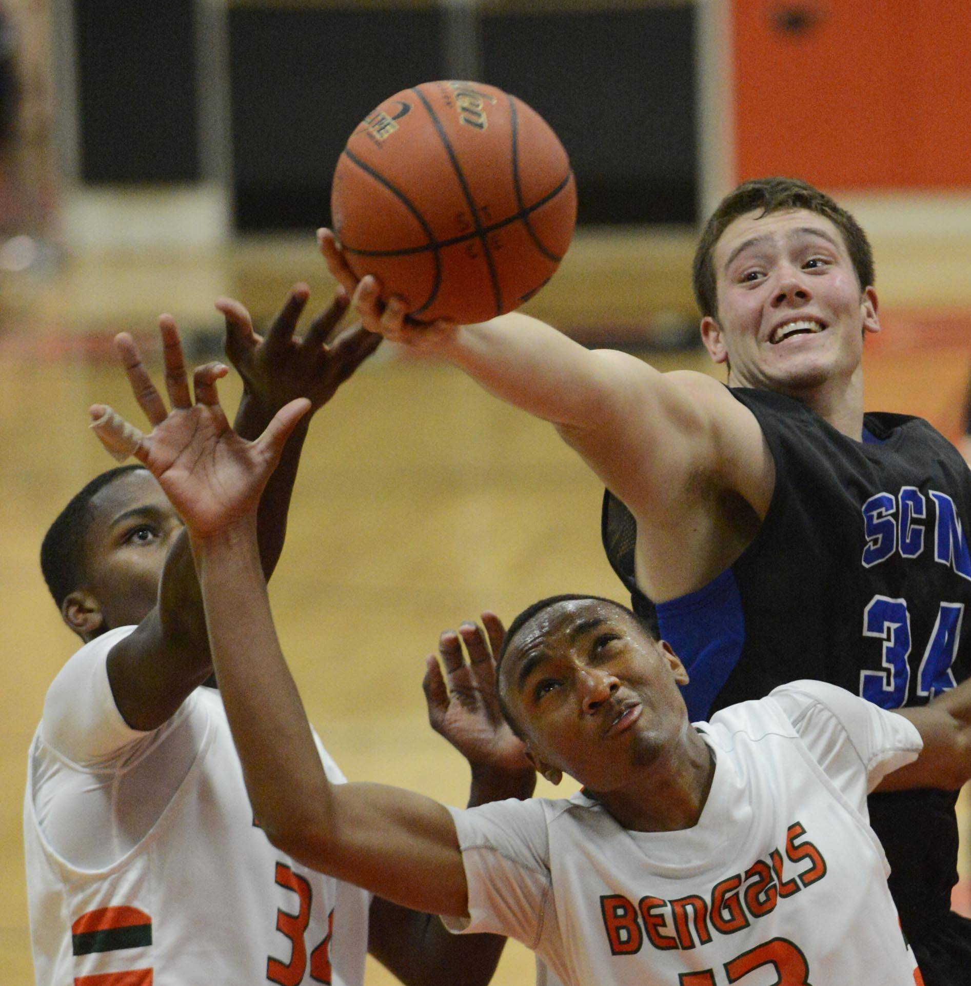 St. Charles North's Garrett Johnson grabs a rebound over Plainfield East's Myles Ward and Malik Binns Tuesday in St. Charles.