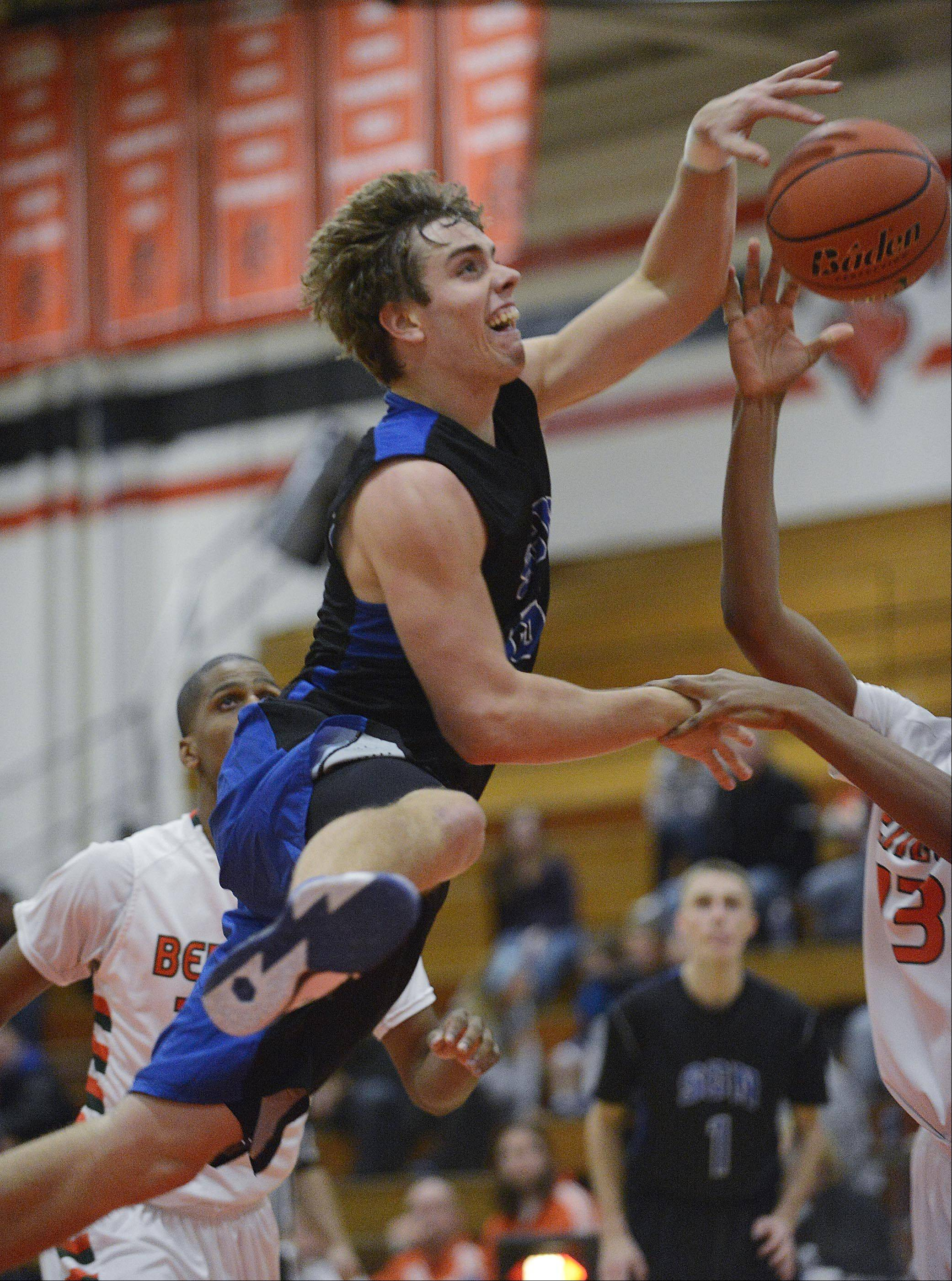 St. Charles North's Erik Miller loses the ball as he is grabbed by Plainfield East's Myles Ward Tuesday in St. Charles. No foul was called.