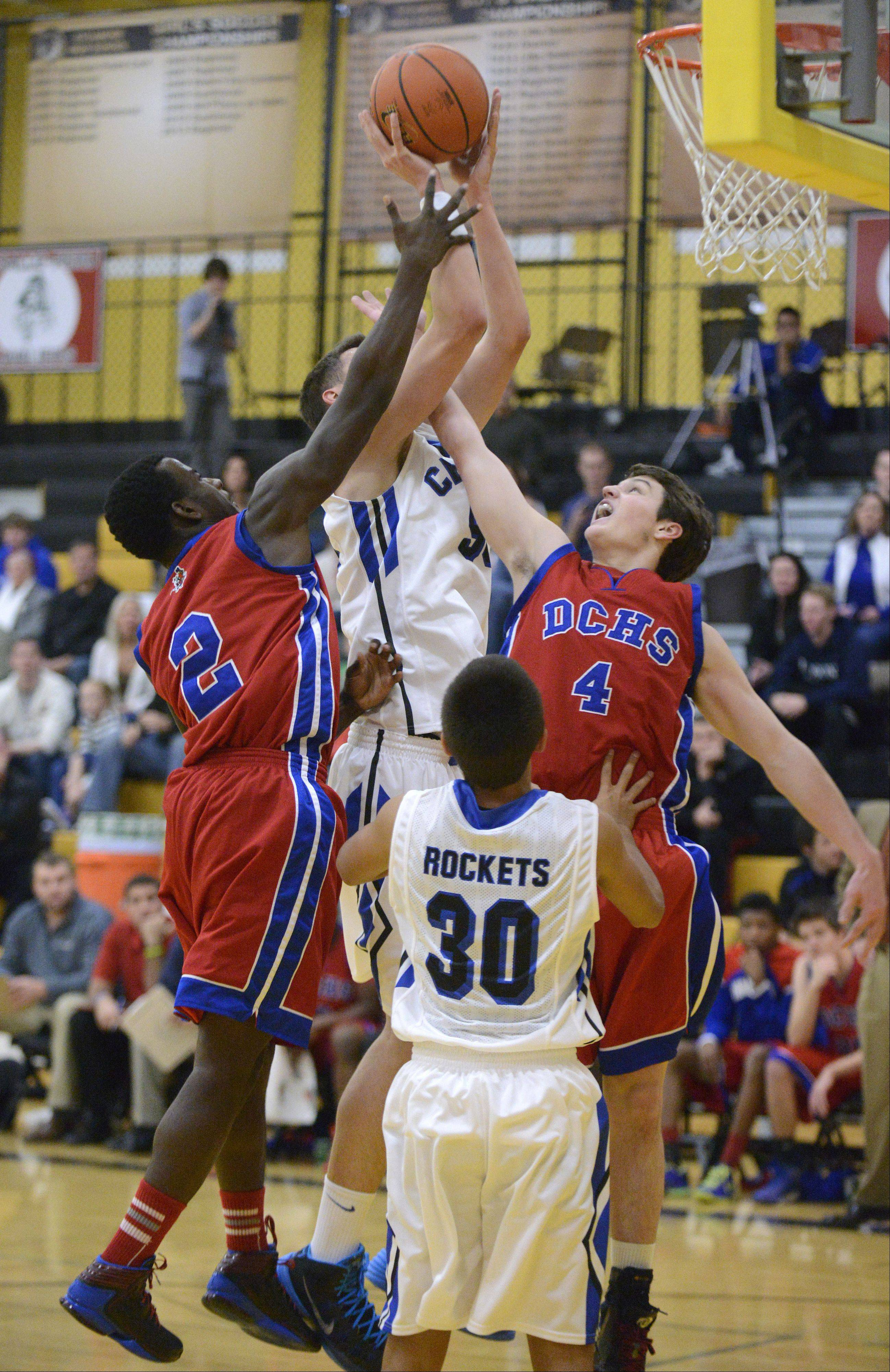 Burlington Central's Duncan Ozburn sinks a shot despite being swarmed by Dundee-Crown's Malik Dunner (2) and Sam Buckley in the first quarter on Tuesday, November 26.