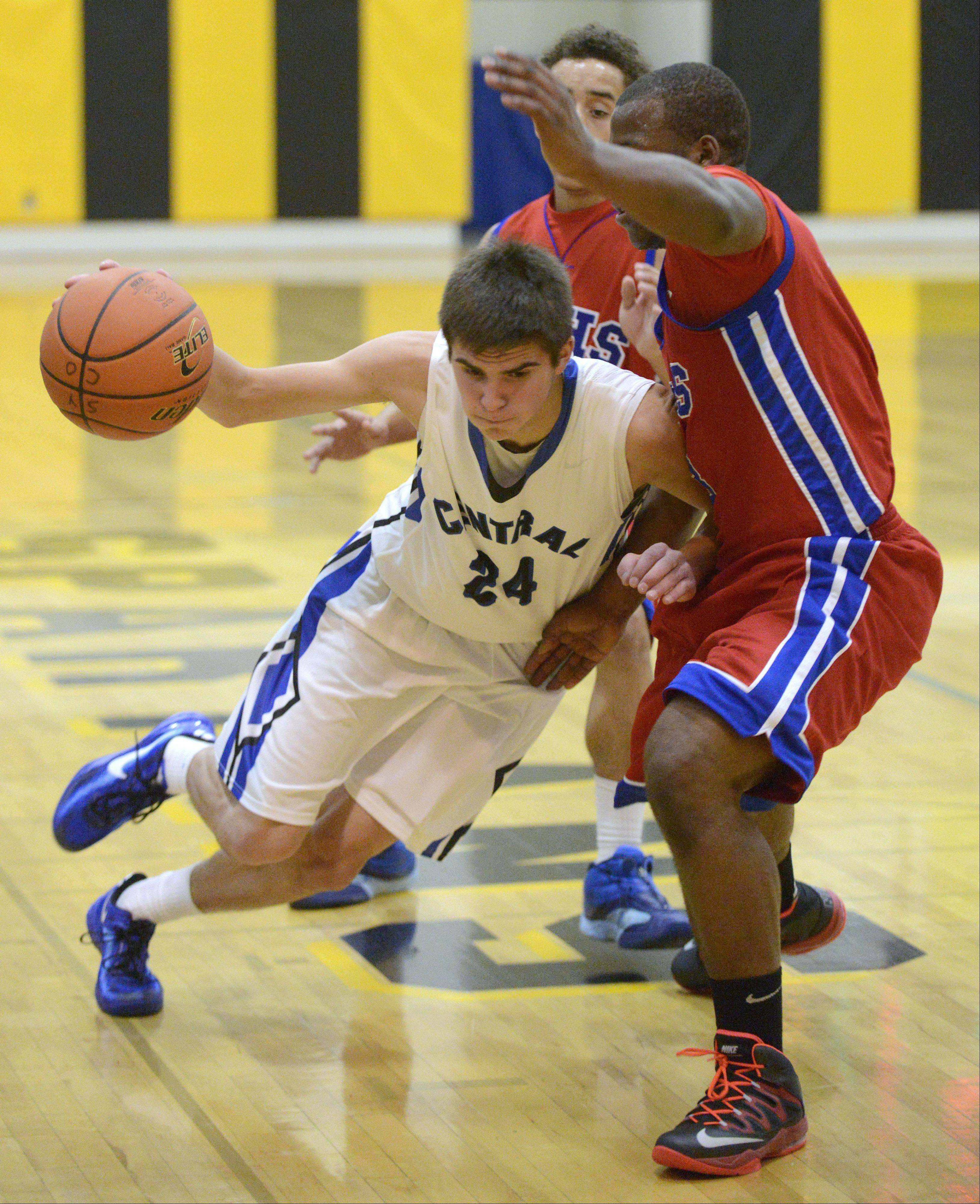 Burlington Central's Brett Rau forces his way to the hoop around Dundee-Crown's Cordero Parson in the first quarter on Tuesday, November 26.