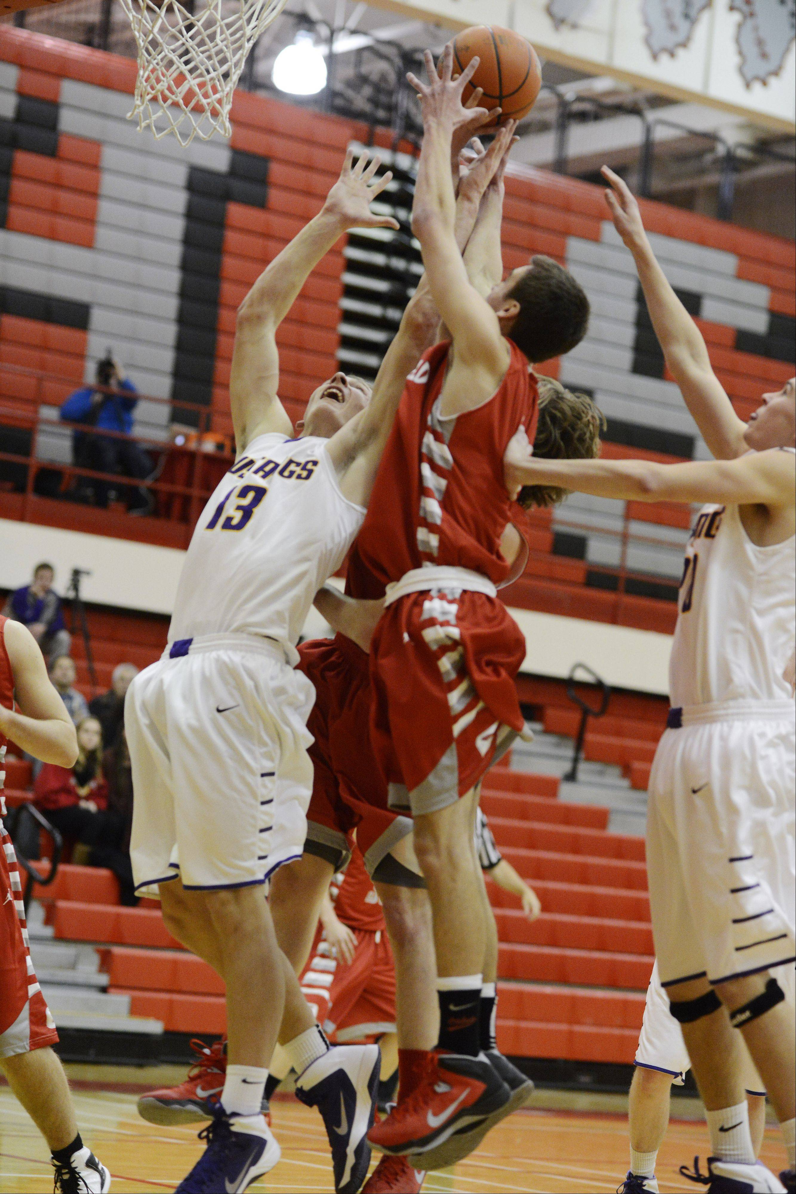 Rolling Meadows' Matt Dolan, left, and Pat Kramp, right, leap for a rebound against Deerfield's Jack Gurvey during Tuesday's game in Palatine.