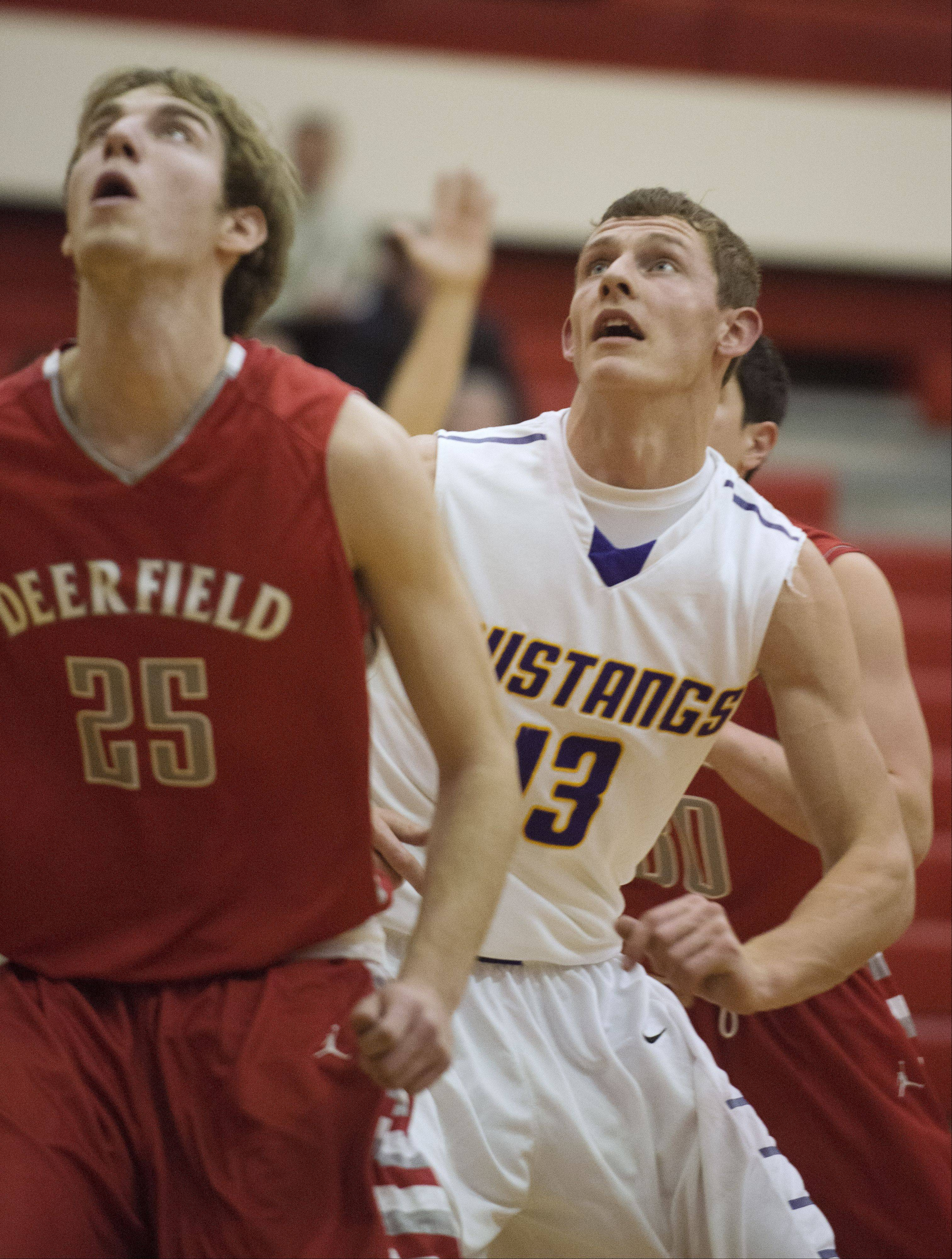 Rolling Meadows forward Matt Dolan, right, looks for a rebound against Deerfield.