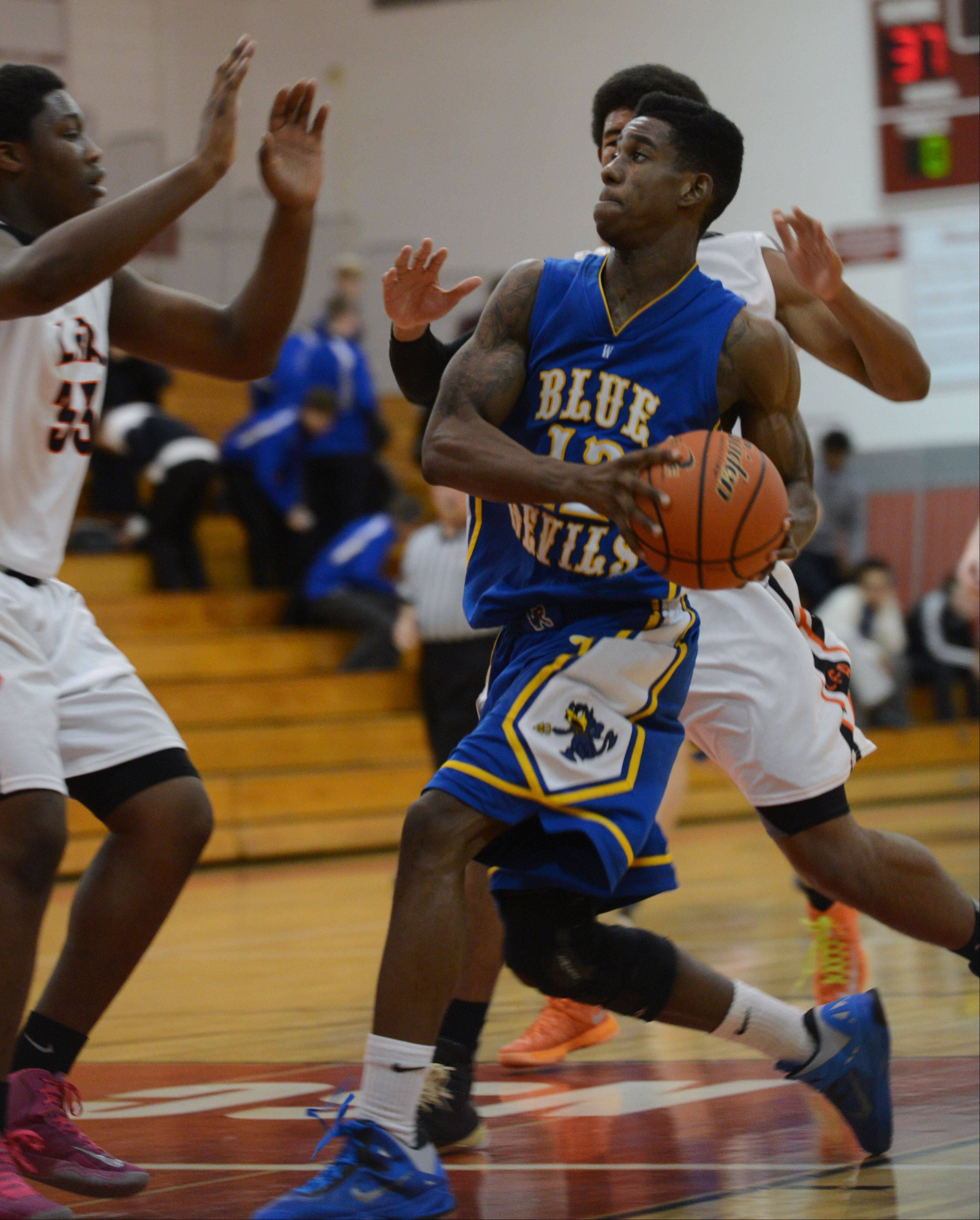 Warren's Greg Swain drives to the hoop against Lake Forest Academy defenders Wednesday in Mundelein.