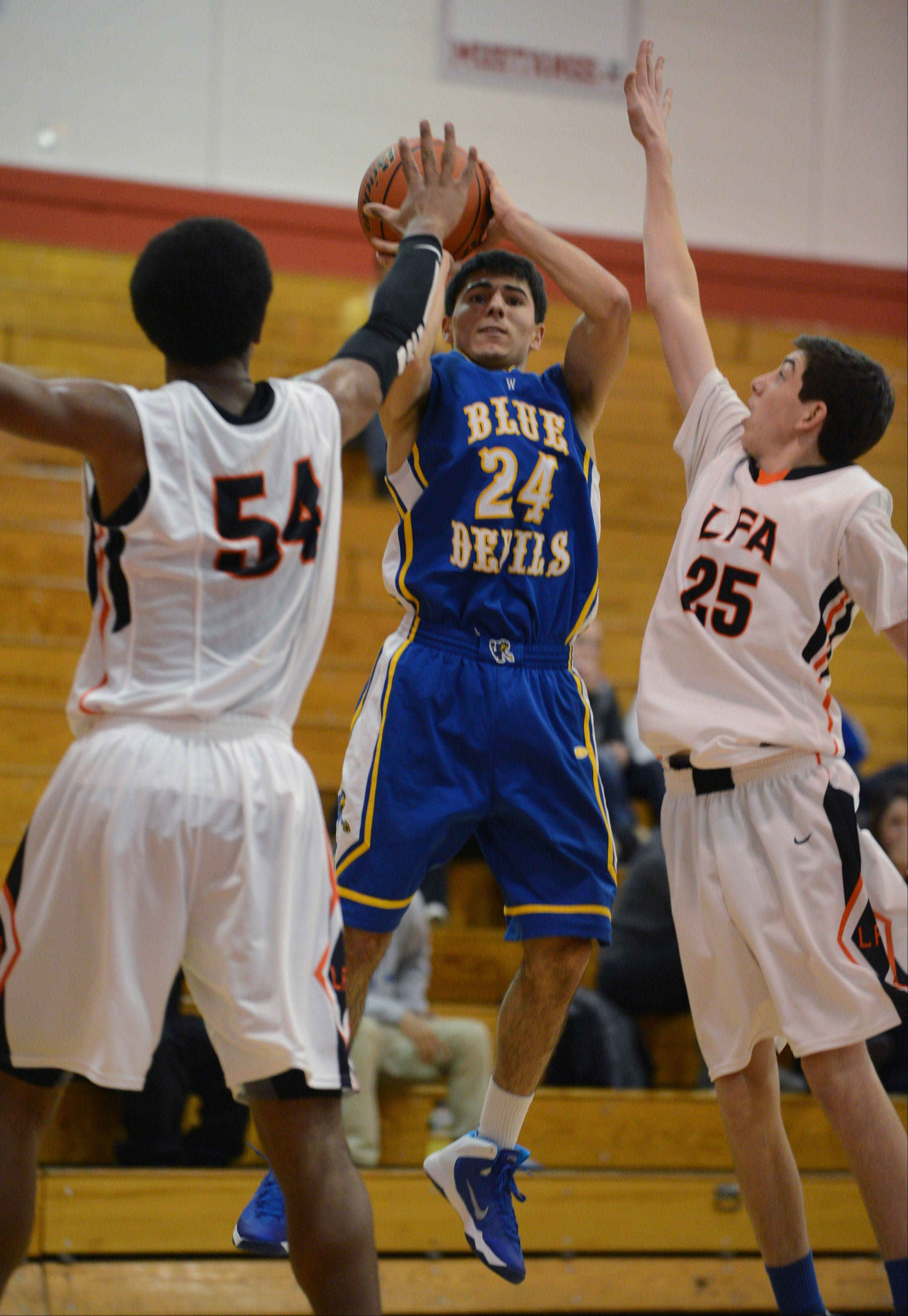 Warren's Dominic Cuevas (24) takes a shot over Lake Forest Academy's Diago Quinn (54) and Ryan Clamage on Wednesday at Mundelein.