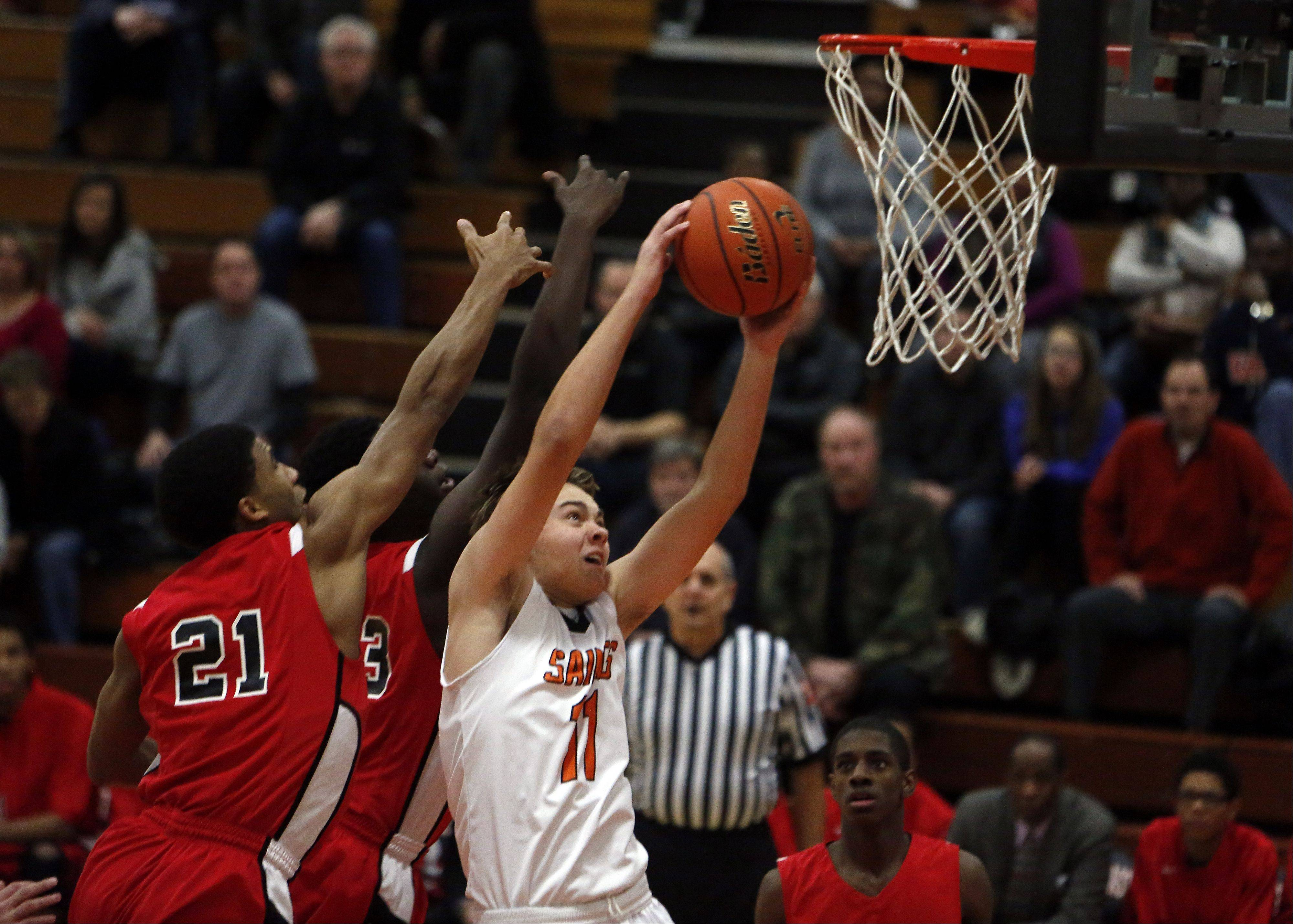 St. Charles East's Mick Vyzral, 11, goes strong to the hoop past St. Joe's Joffery Brown.