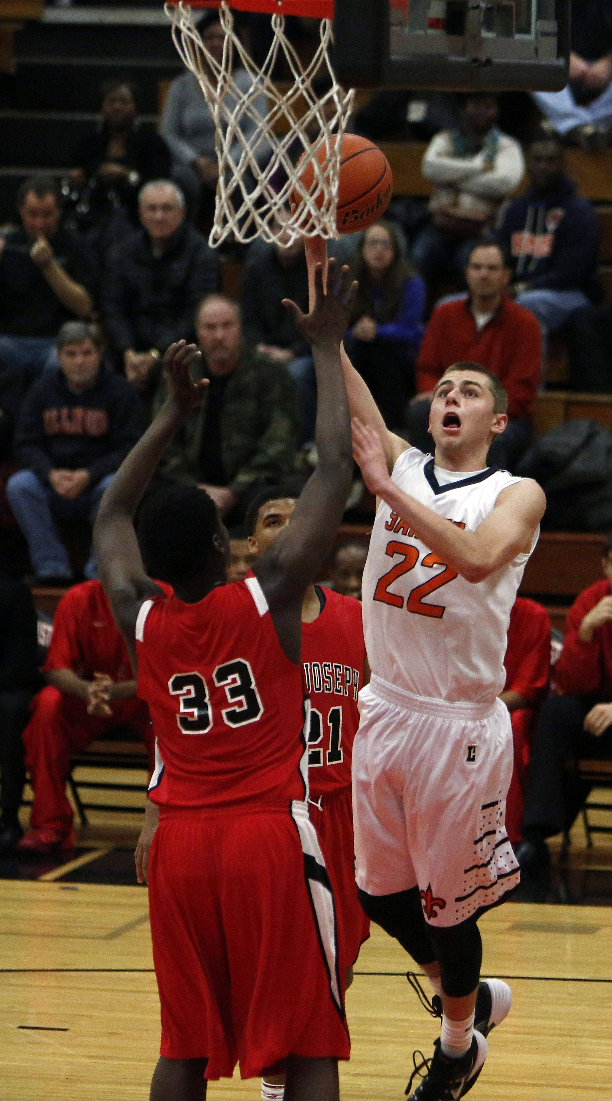 St. Charles East's James McQuillan, 22, makes his way past St. Joeseph's Joffery Brown, 21, and Lavon Thomas, 33, during St. Charles East's 55th annual Ron Johnson Thanksgiving Tournament Friday in St. Charles.