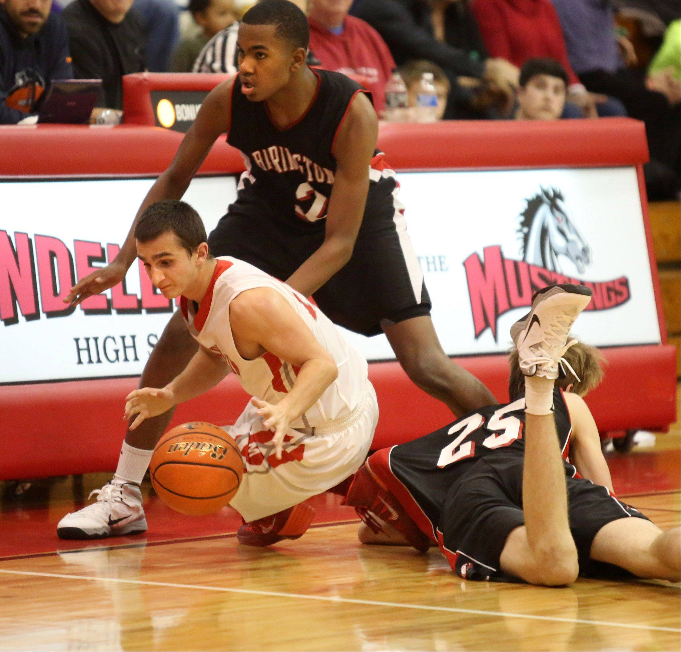 Mundelein guard Nick Filippo tries to keep his dribble after tripping over Barrington defender Rapolas Ivanauskas, flat on the floor, with Barrington's Chris Lester trying to regain position on Friday at Mundelein.